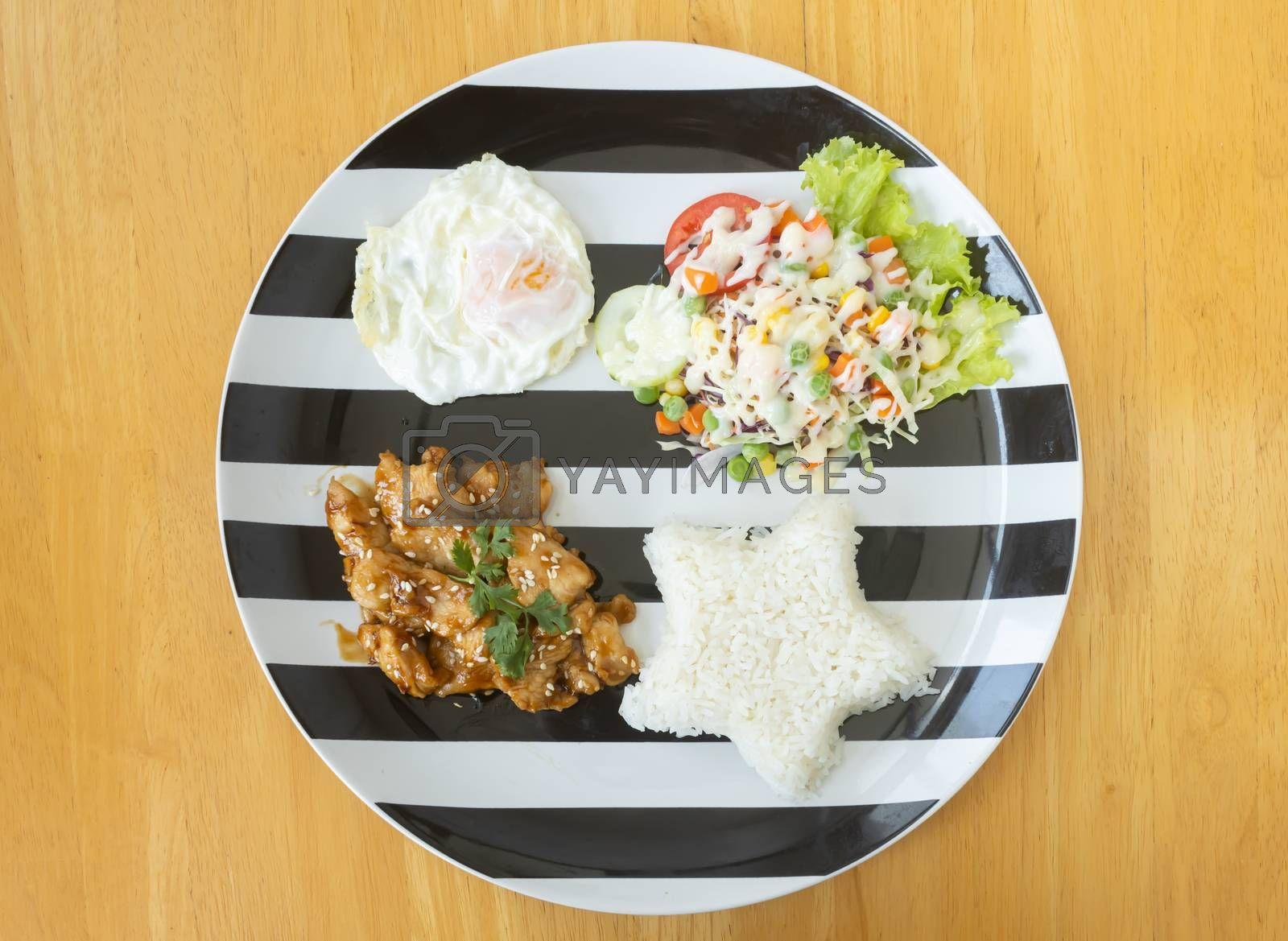 Fried Chicken with Garlic and Pepper and Fried Egg and Vegan Salad and Rice in Dish on Wood Table with Natural Light on Flatlay View