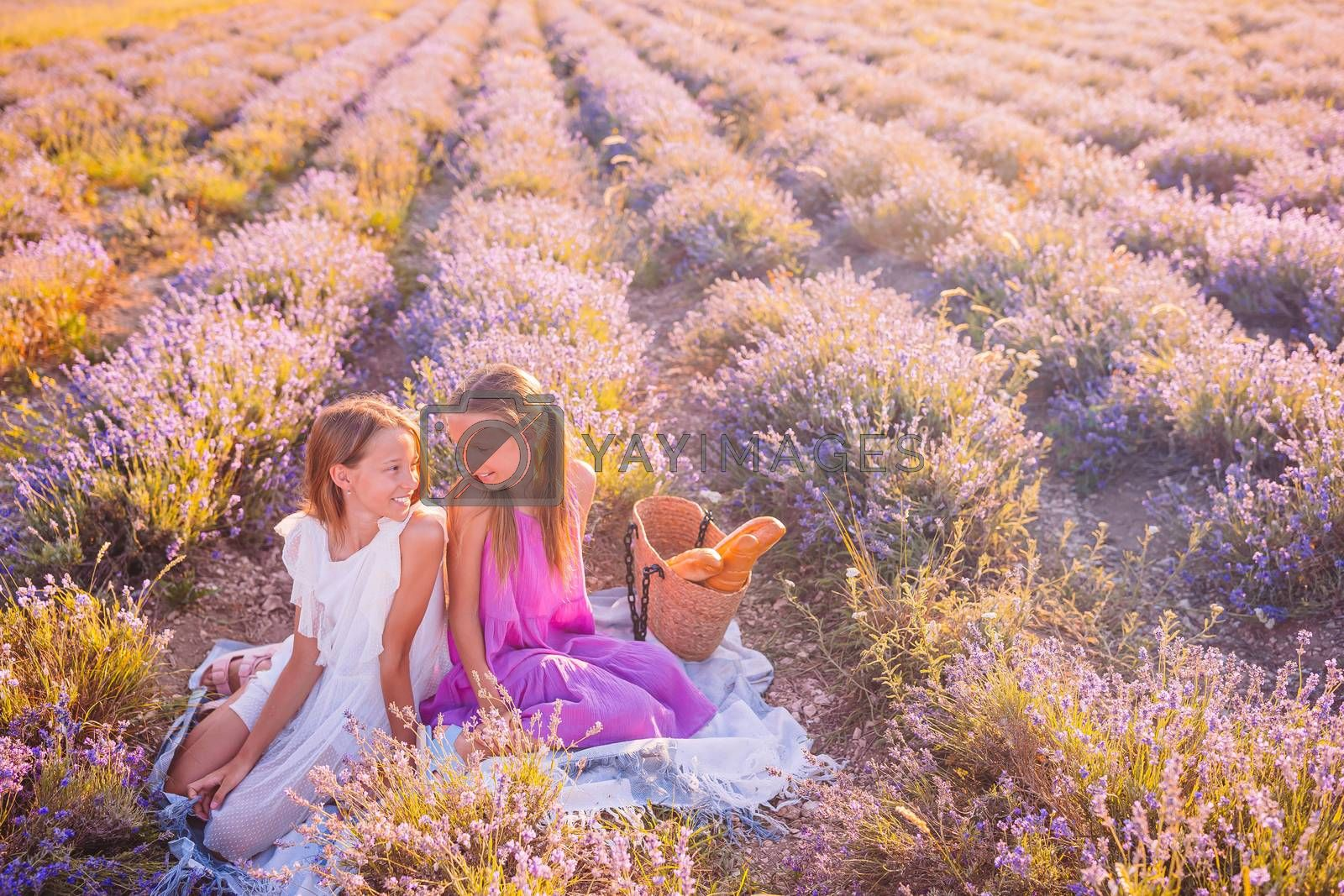 Little adorable girls in lavender flowers field on picnic