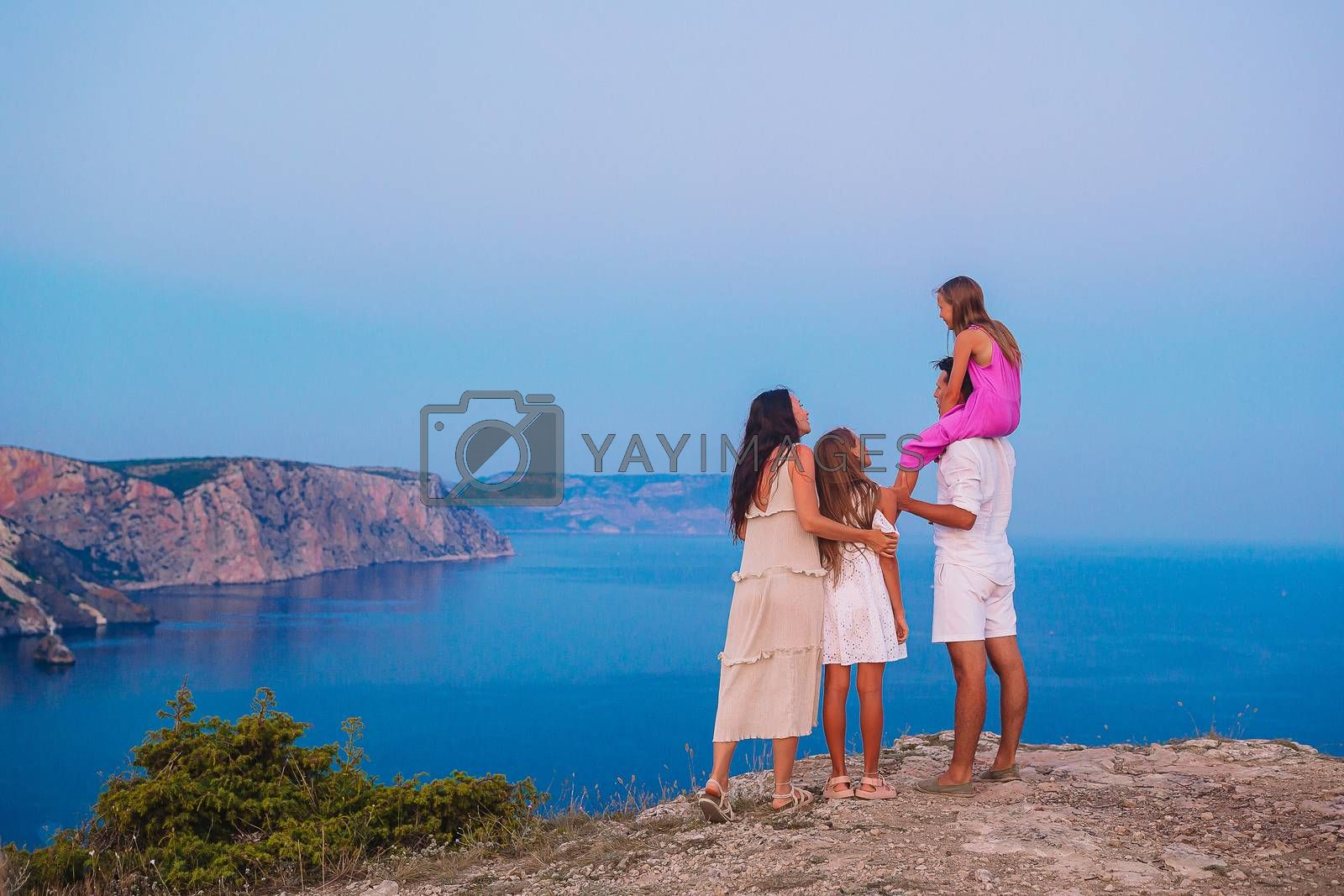 Happy family stands against mountains sunset. Travel tourism adventures concept