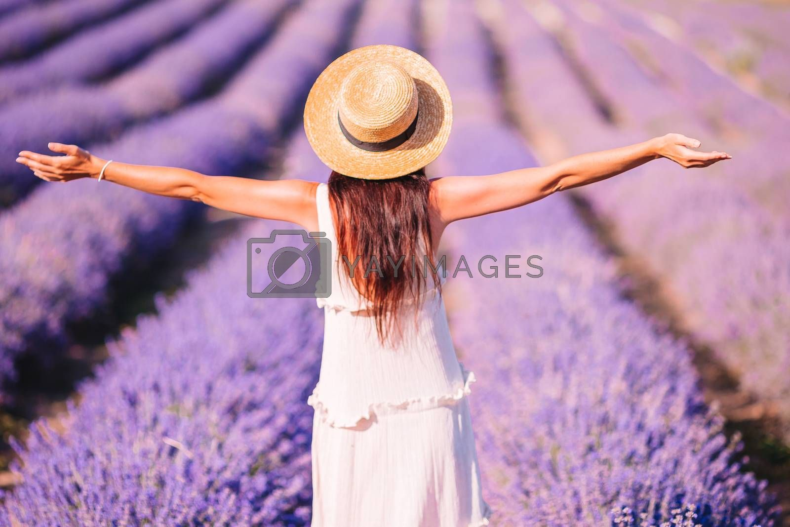 Beautiful young woman relaxing and having fun on purple flower lavender field