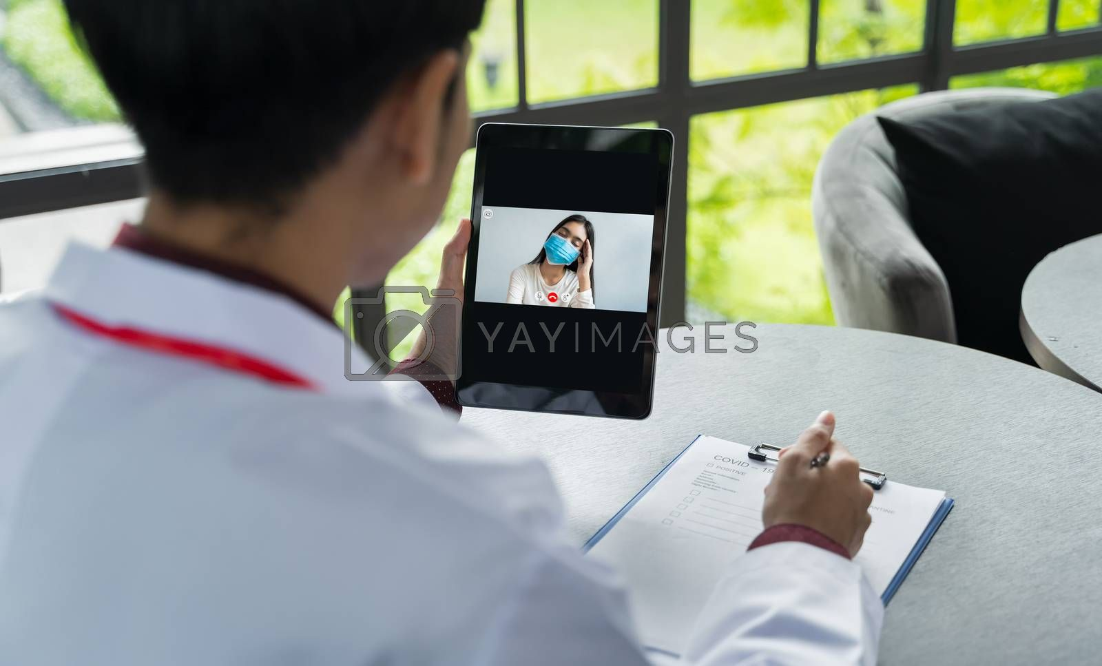 The doctor's back view is communicating with the patient wear a mask via tablets. Doctors are using Telemedicine technology to interact with patients via video conference for keep social distancing