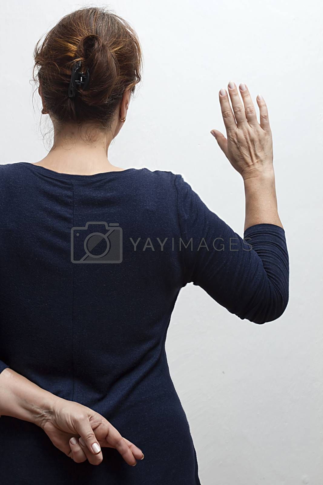 Woman takes an oath and holds her crossed fingers behind her back.