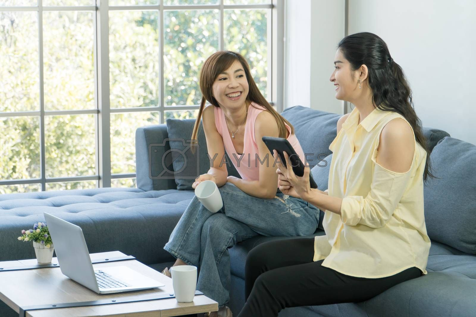 Two attractive Asian women are talking at home happily. Freelance women share casual wear, meetings, and computer technology together. learning use the internet  chatting with people on social media