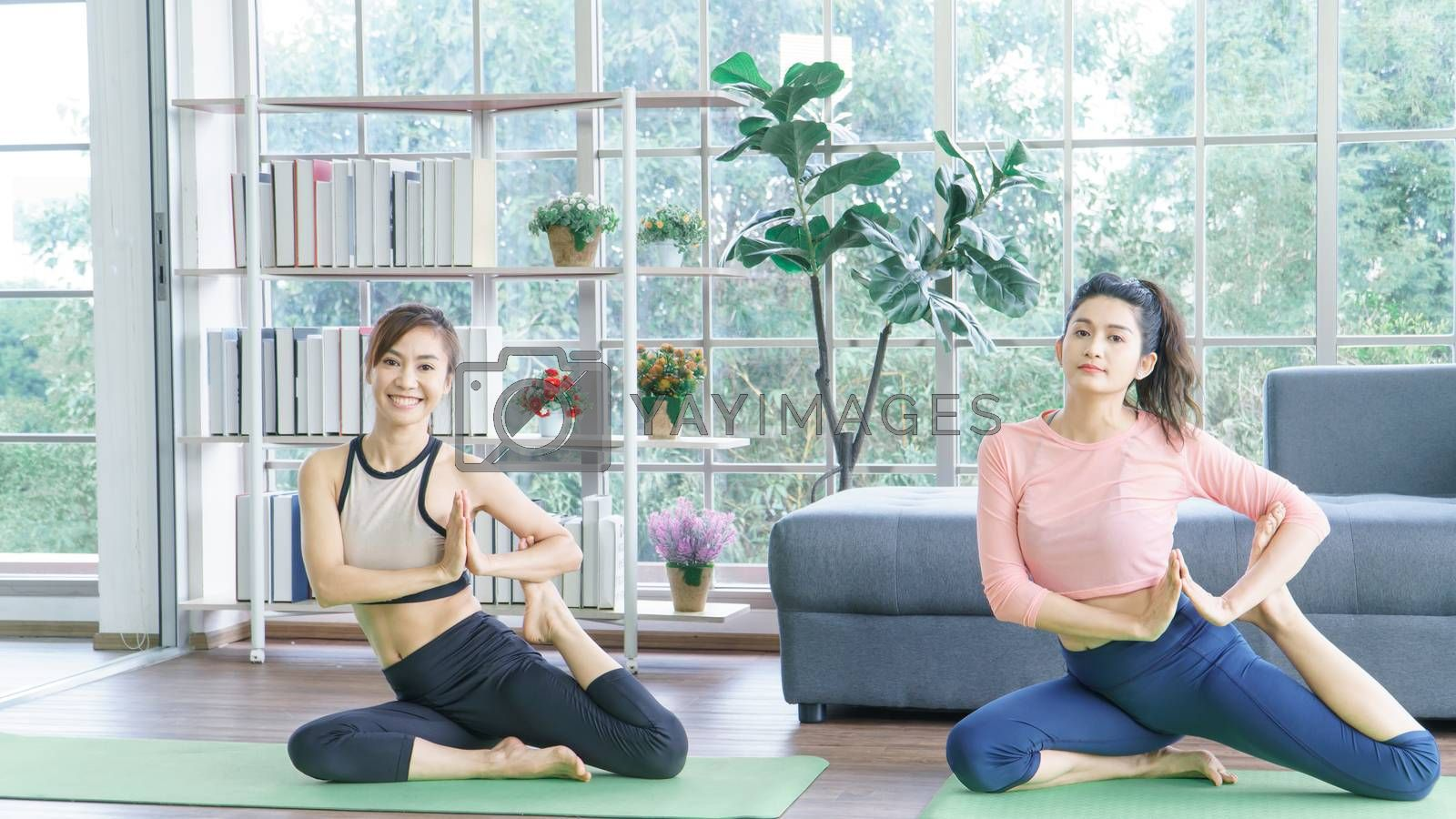 Attractive middle-aged women in Asia practice yoga, sit meditation For a balanced life at home. Sporty wears Sportswear to stretch the body with asana administration positions.