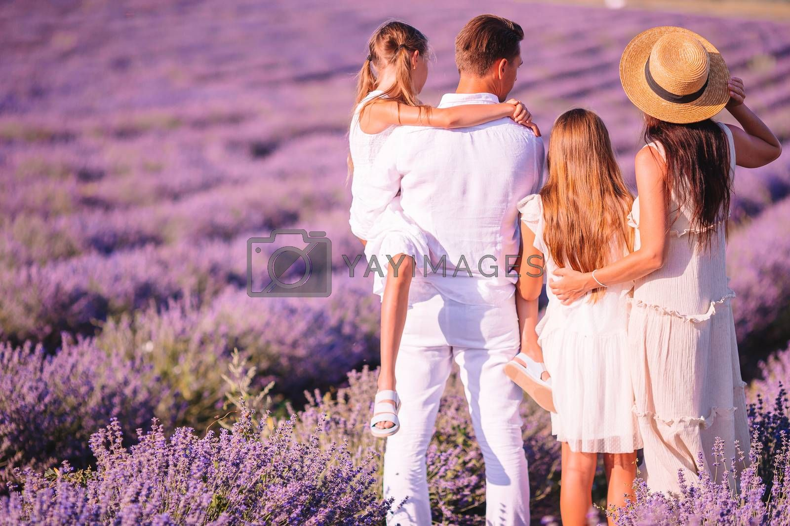Beautiful young family on purple flower lavender field. Family vacation