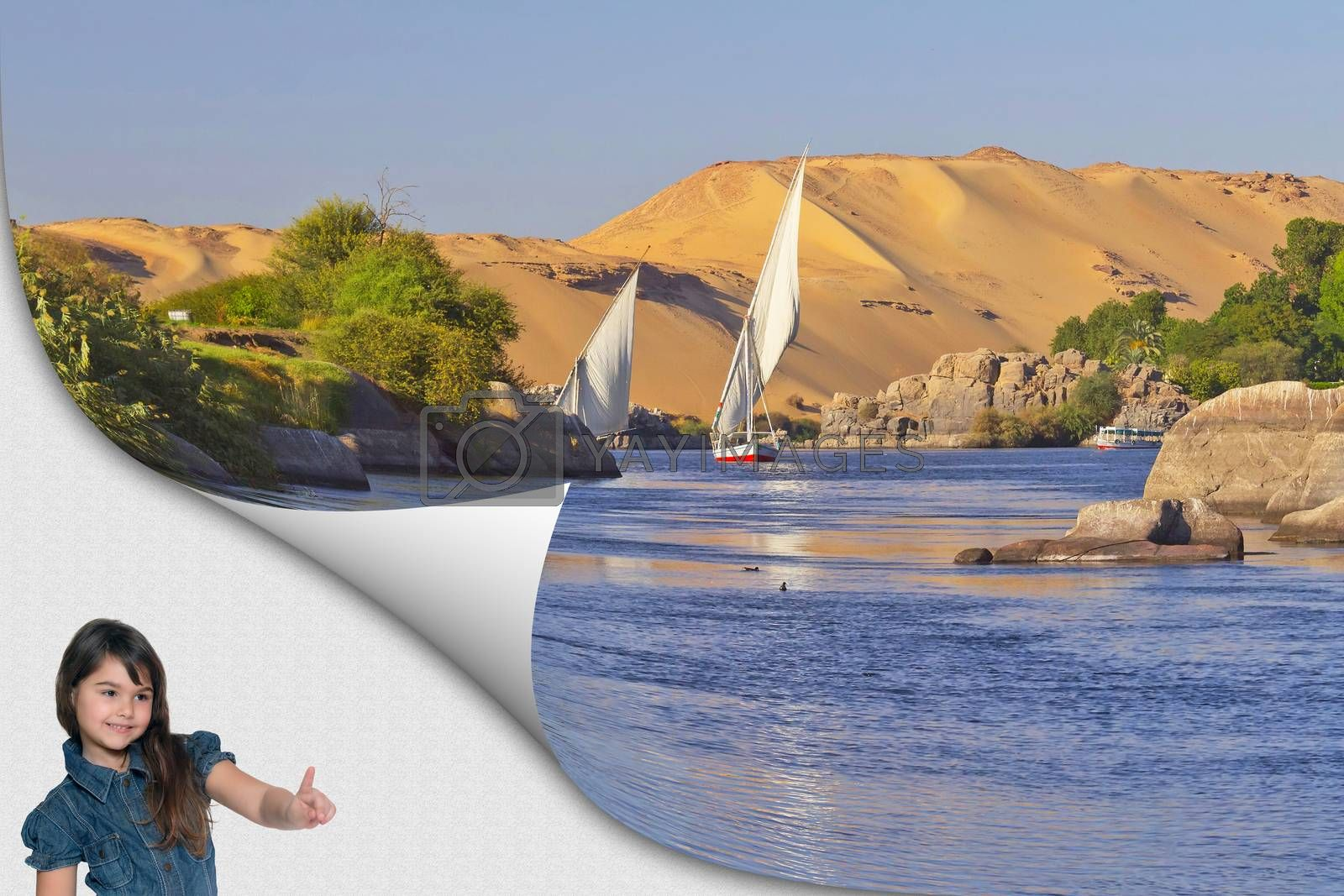 Cute tanned little girl standing in an exposed corner of the photo is pointing at the famous sailboats sailing on the Nile near Aswan with sand dunes in the background. Egypt.
