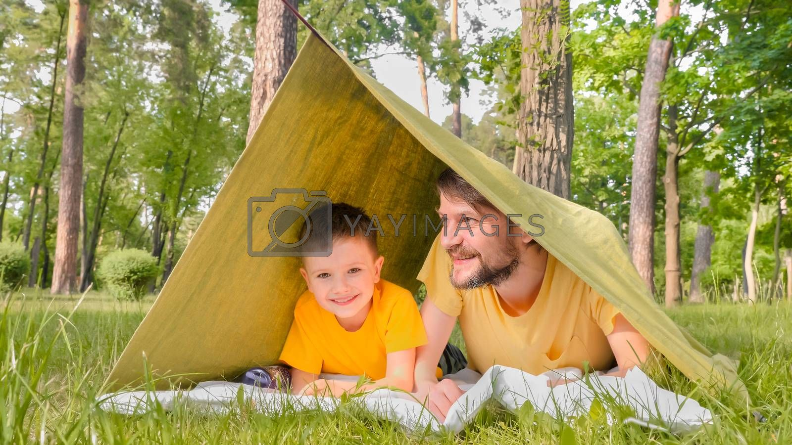 Smiling father with son in tent on green grass having fun. Family vacation in nature in the park. Father and son communicate in a house with a blanket. Travel close to home. Childhood concept.