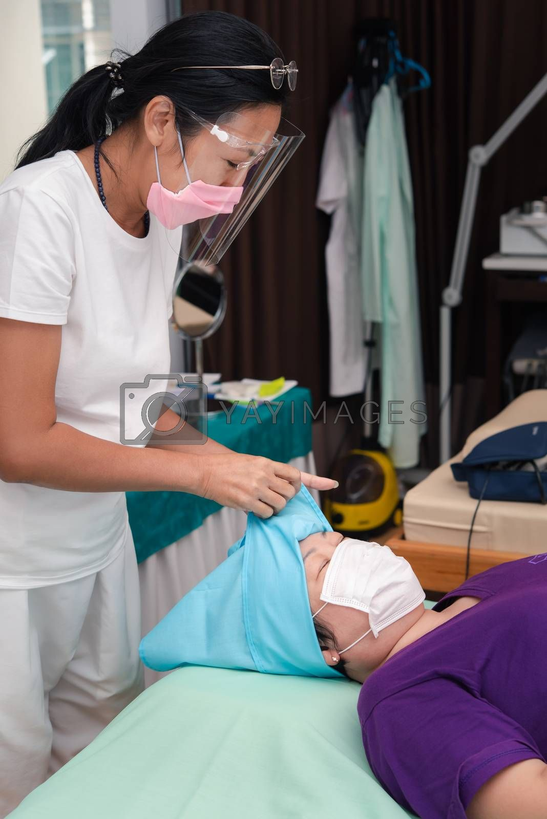 Bangkok, Thailand - May 30, 2020 : Unidentified Asian woman eyebrow tattooing by specialist in Eyebrow tattoo or embroidery clinic use COVID-19 prevention policy protect by use mask and face shield