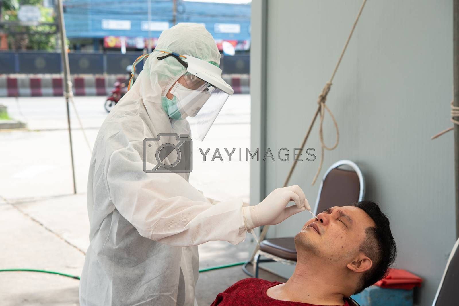 Bangkok, Thailand - May 17, 2020 : Unidentified doctor in PPE suit and asian man patient check by COVID-19 specimen performing a nasopharyngeal or oropharyngeal swab from nasal and oral at hospital