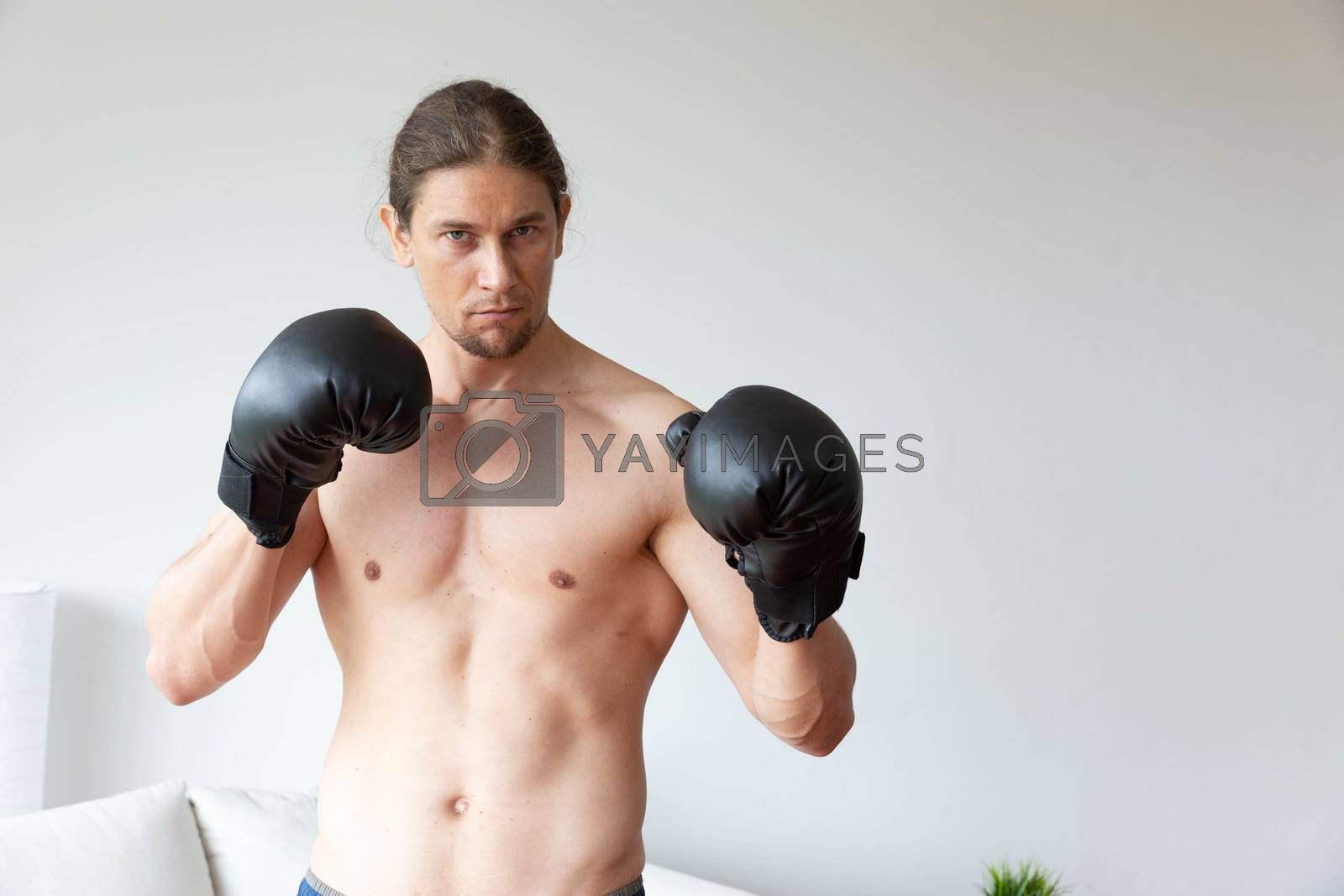 A sport man has boxing training in his living room at home
