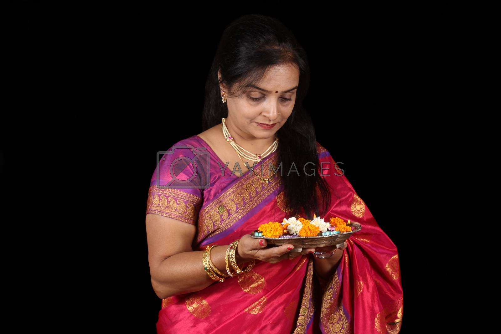 An Indian woman with a plate of flowers and lamp for a traditional prayer, on black studio background.
