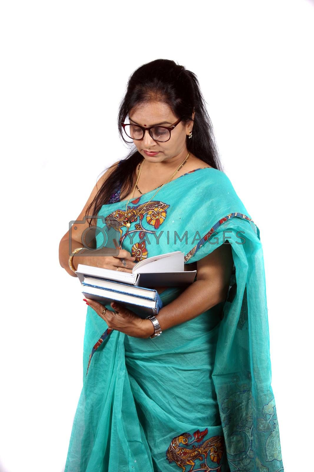 A middle aged Indian woman who is a teacher reading her books before lecture, on white studio background.