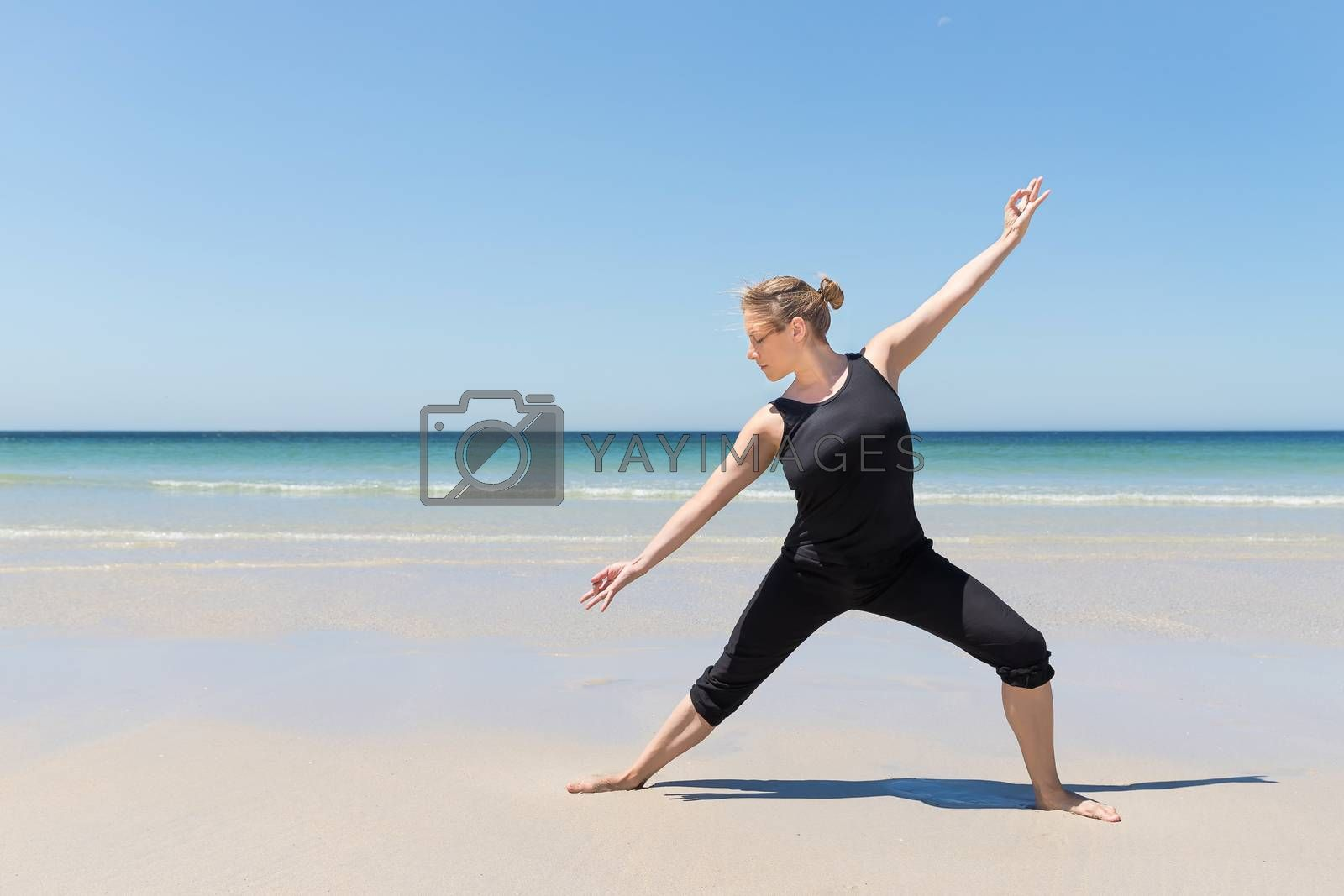 woman in meditation pose at the beach with the sea in the background