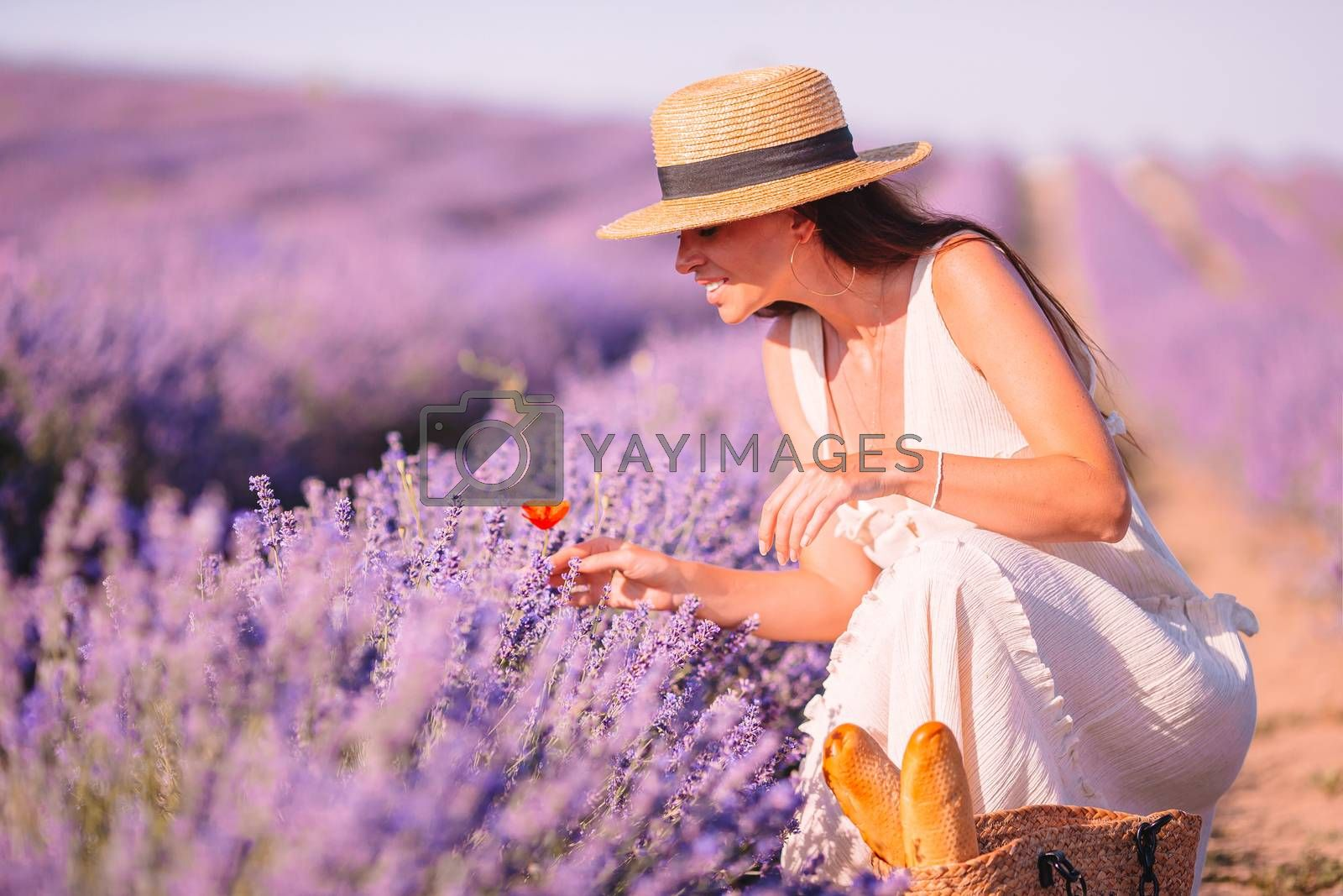 Beautiful young woman on purple flower lavender field found one red poppy