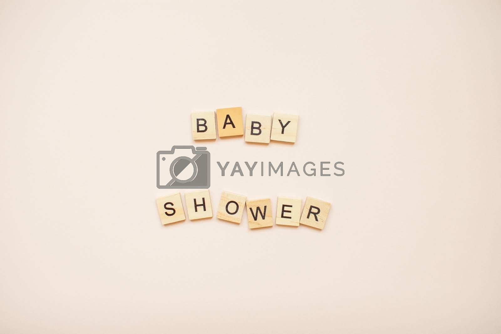 """The inscription """"baby shower"""" made of wooden blocks on a light pink background."""