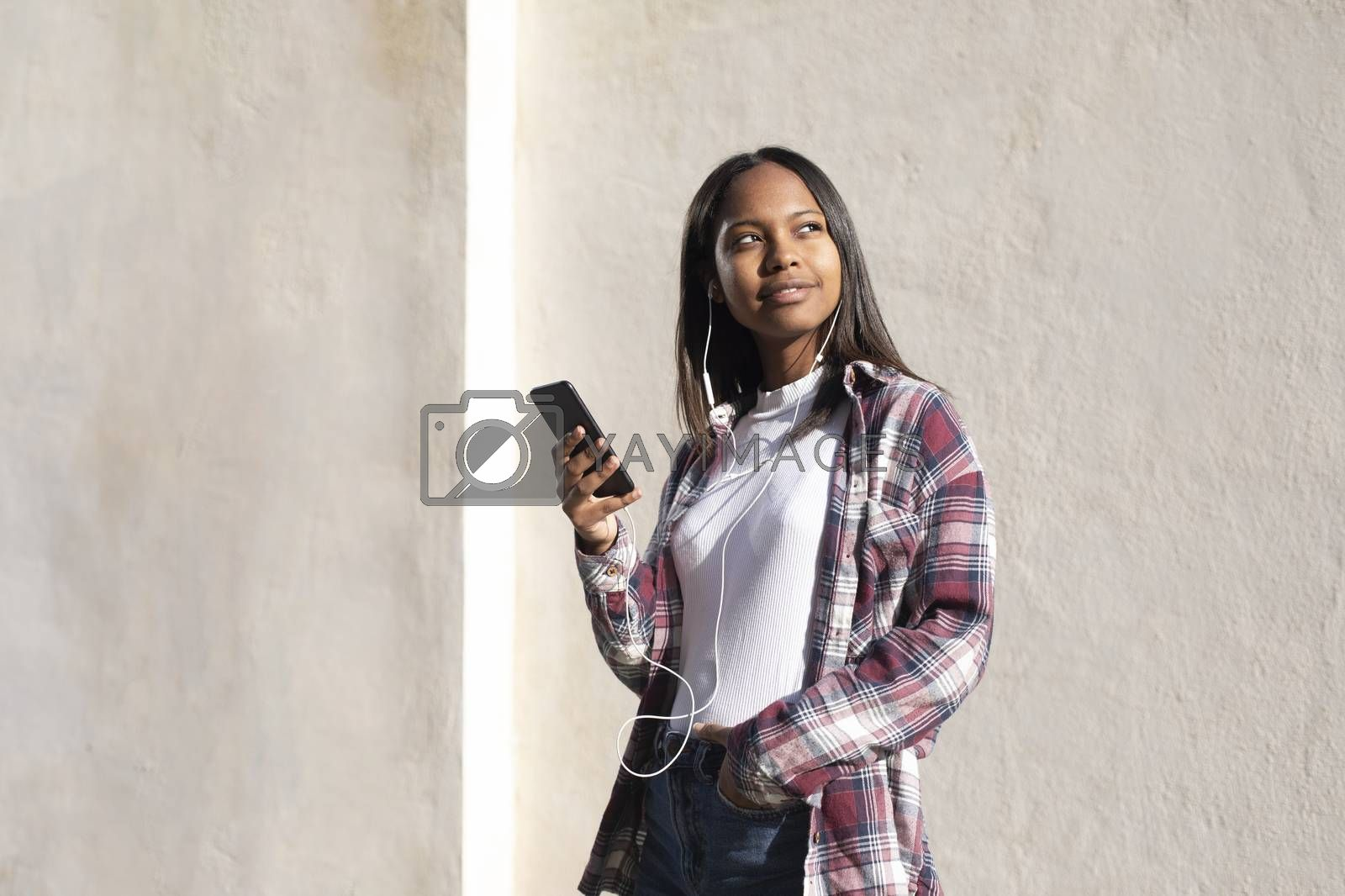 Portrait of African American young woman standing on the street while using a mobile phone
