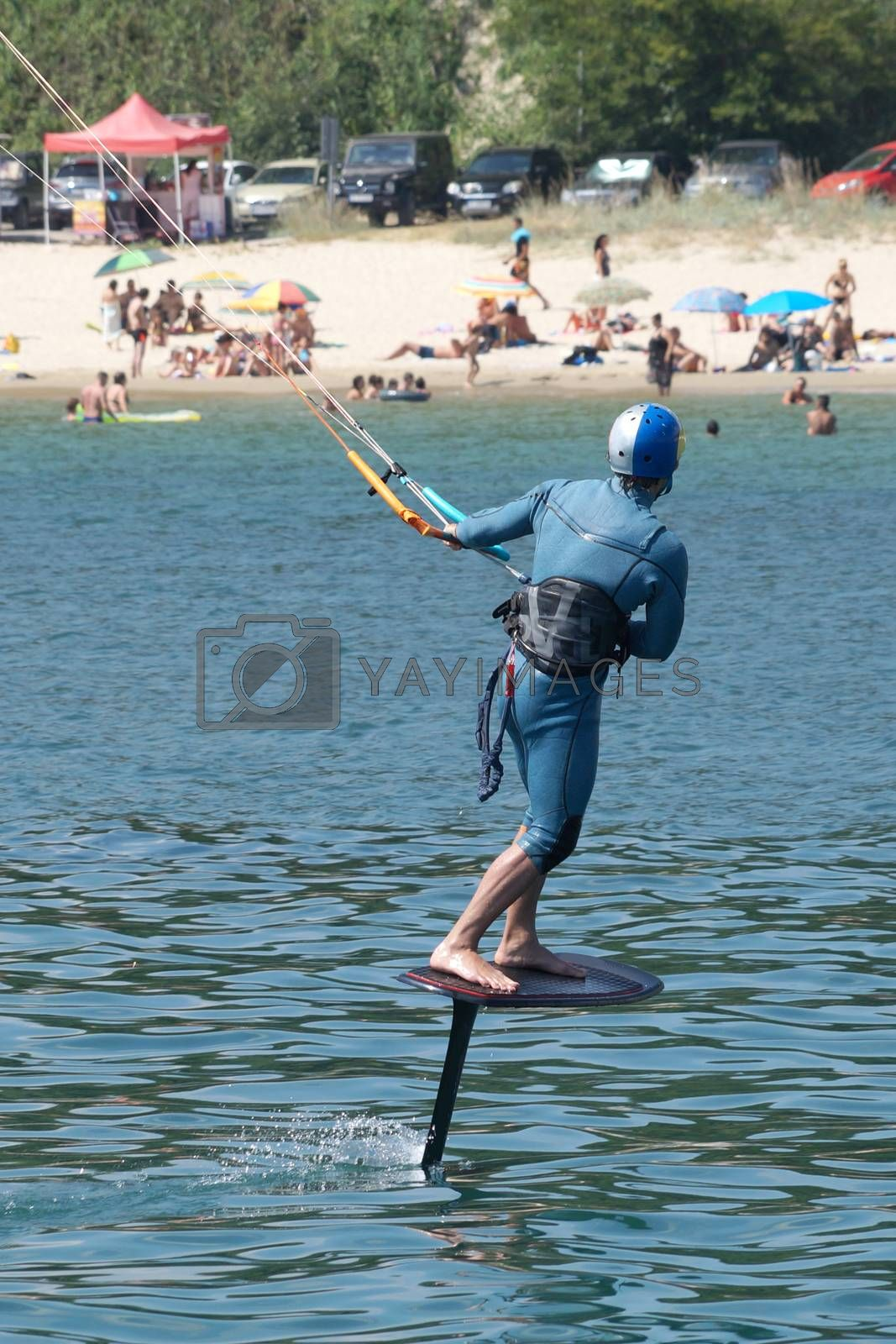 a man is kiting the sea against the background of the beach.