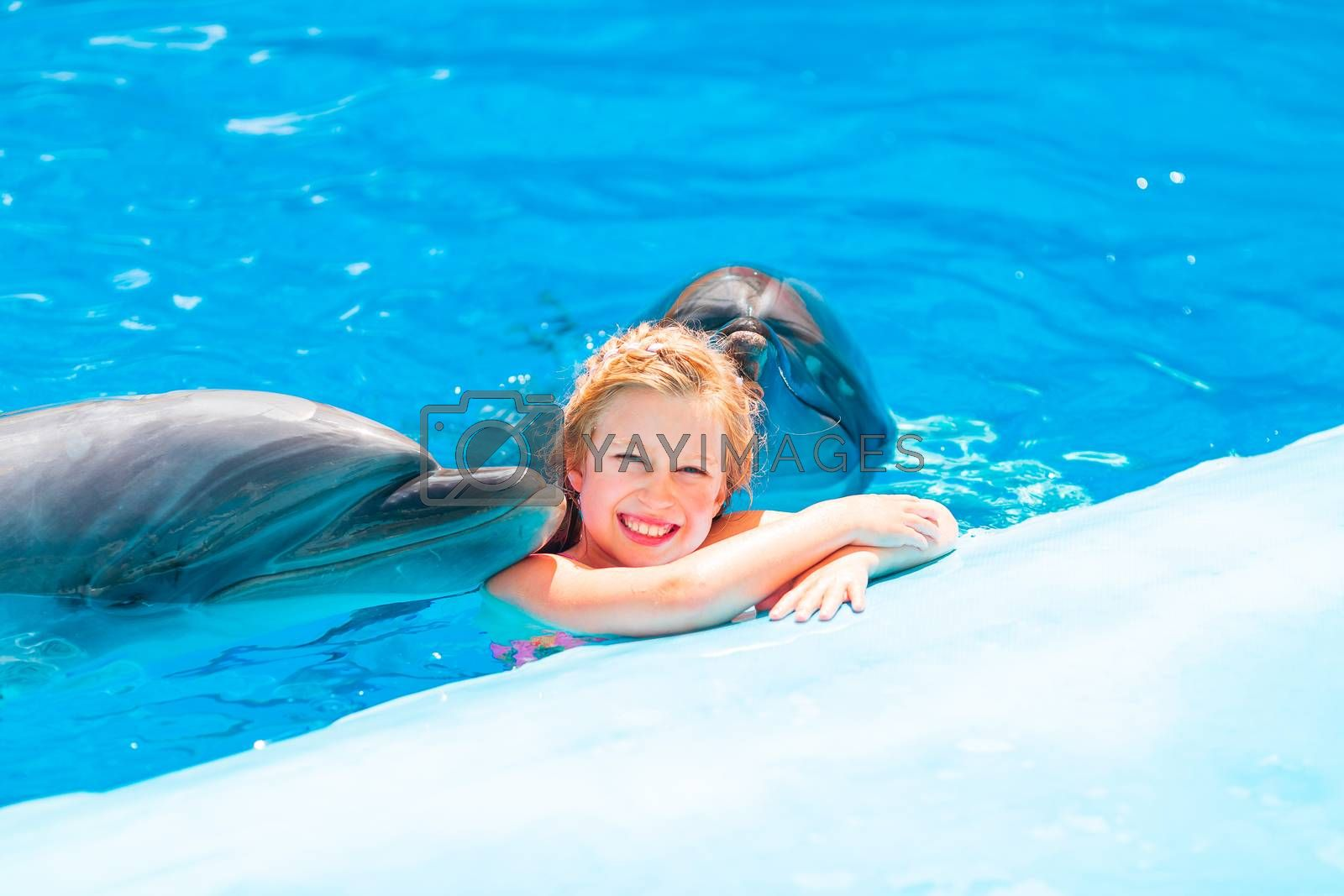 Happy little girl swimming with dolphins in Dolphinarium by Len44ik