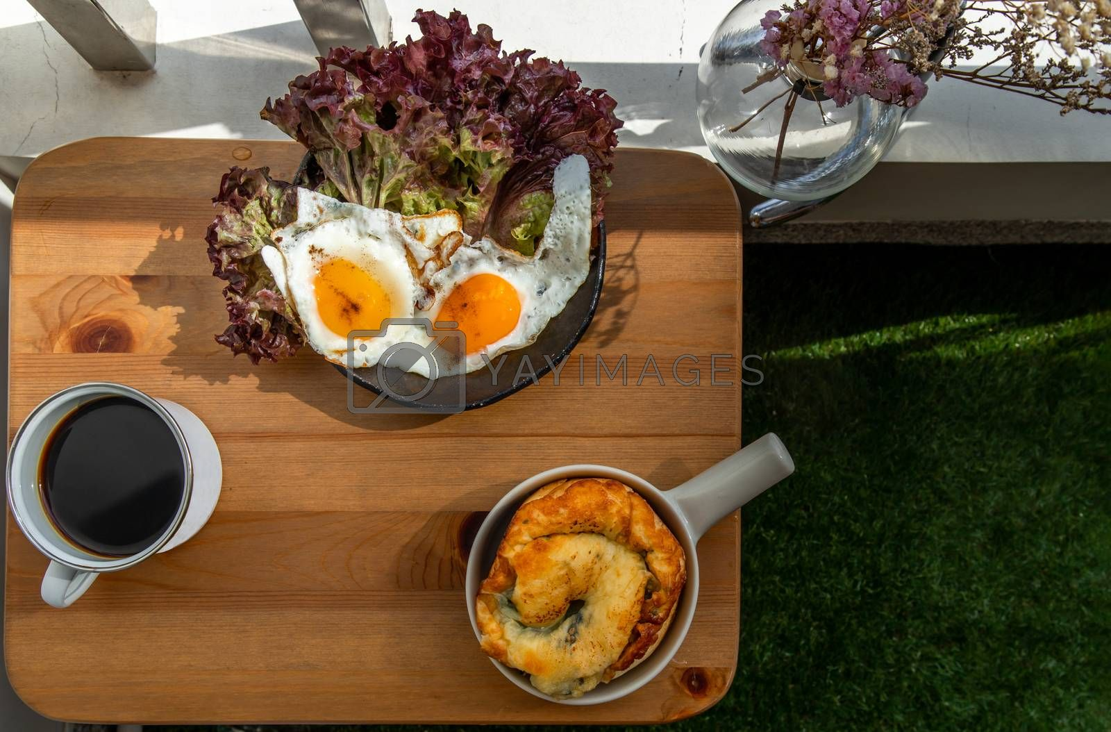 Breakfast with Spinach brioche, Two fried eggs, Oak Leaf lettuce served with Black coffee on wooden table at balcony. Selective focuse.