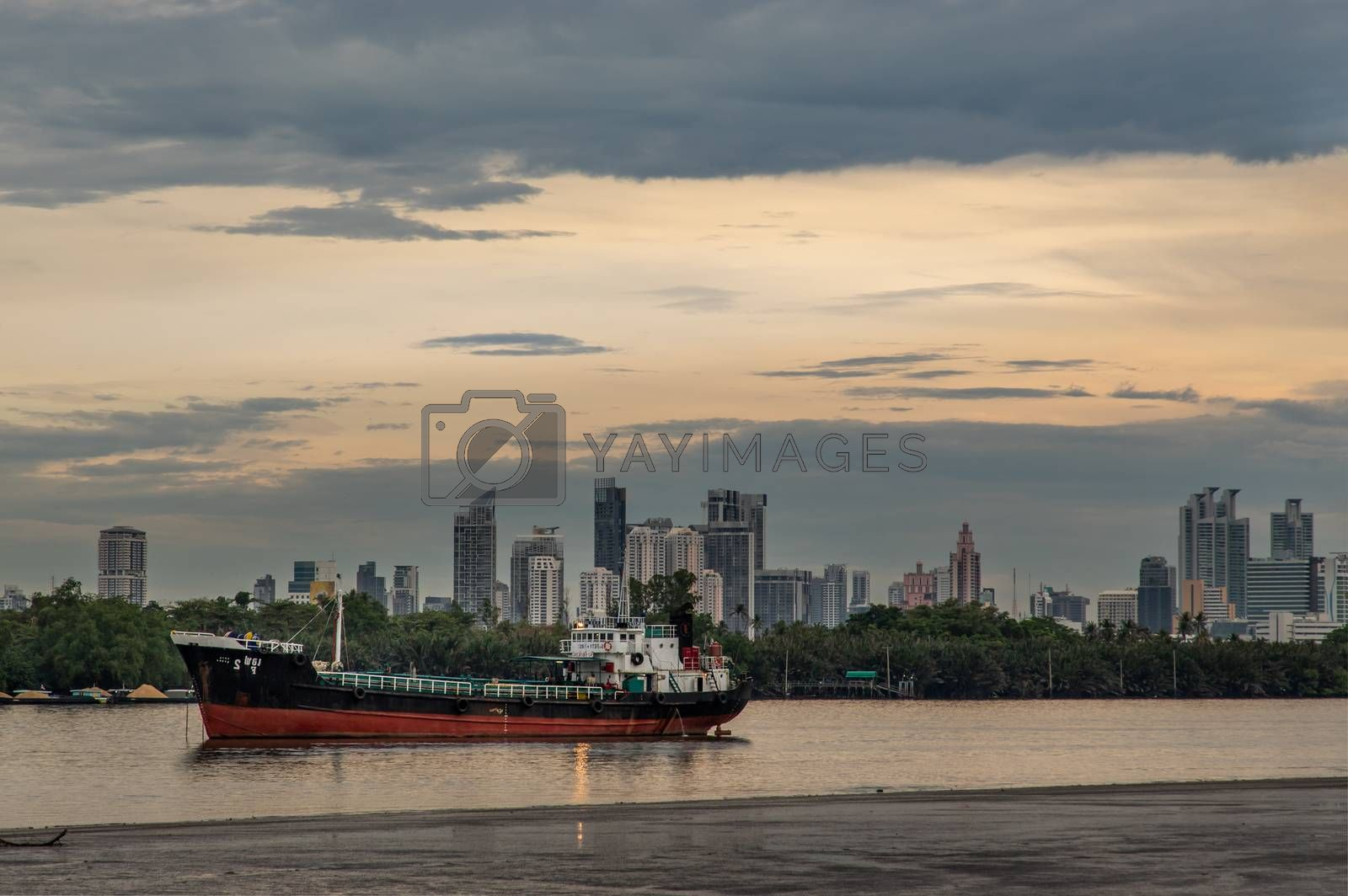 A cargo ship parked in the middle of the Chao phraya river on ev by tosirikul