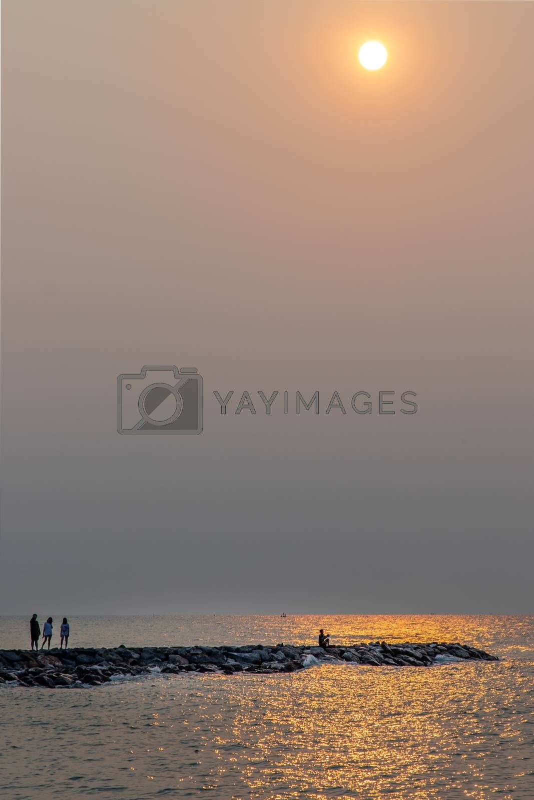 Phetchaburi,Thailand - Mar 15, 2020 : Angler with fishing rod and tourist on at the Calm beach in the morning. Selective focus.