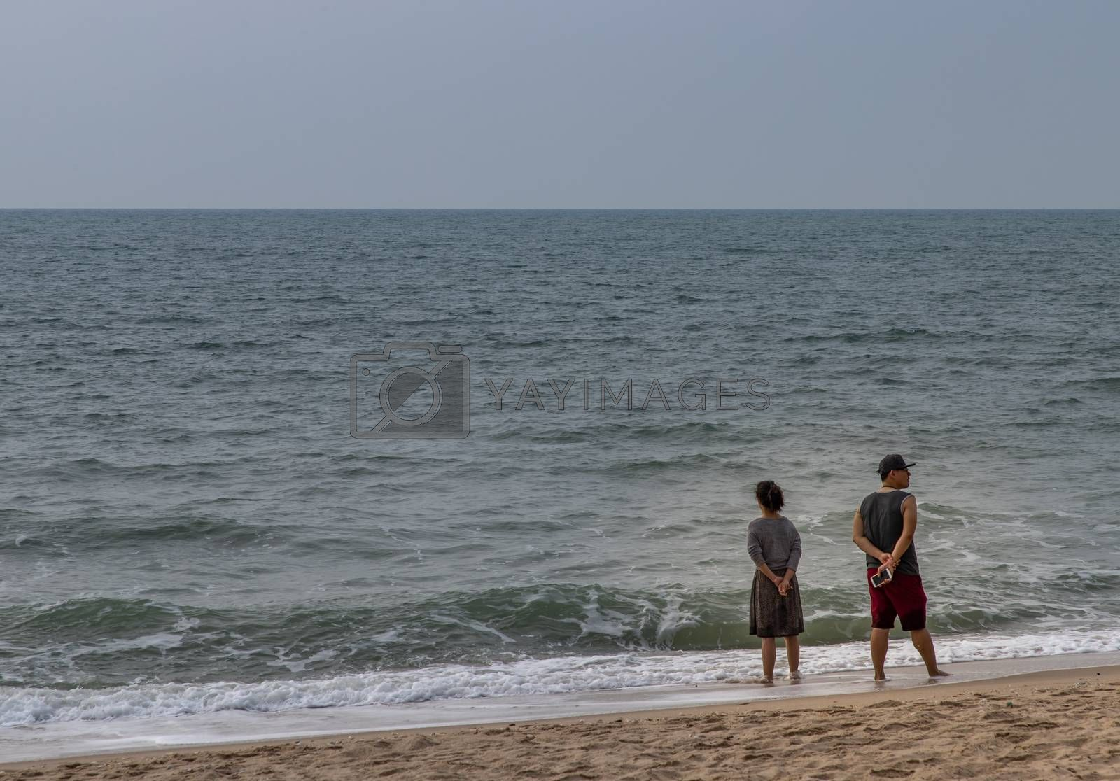 Phetchaburi,Thailand - Mar 15, 2020 : Rear view of tourist man and women standing on beach on a sunny day. Vacation trip. Selective focus.