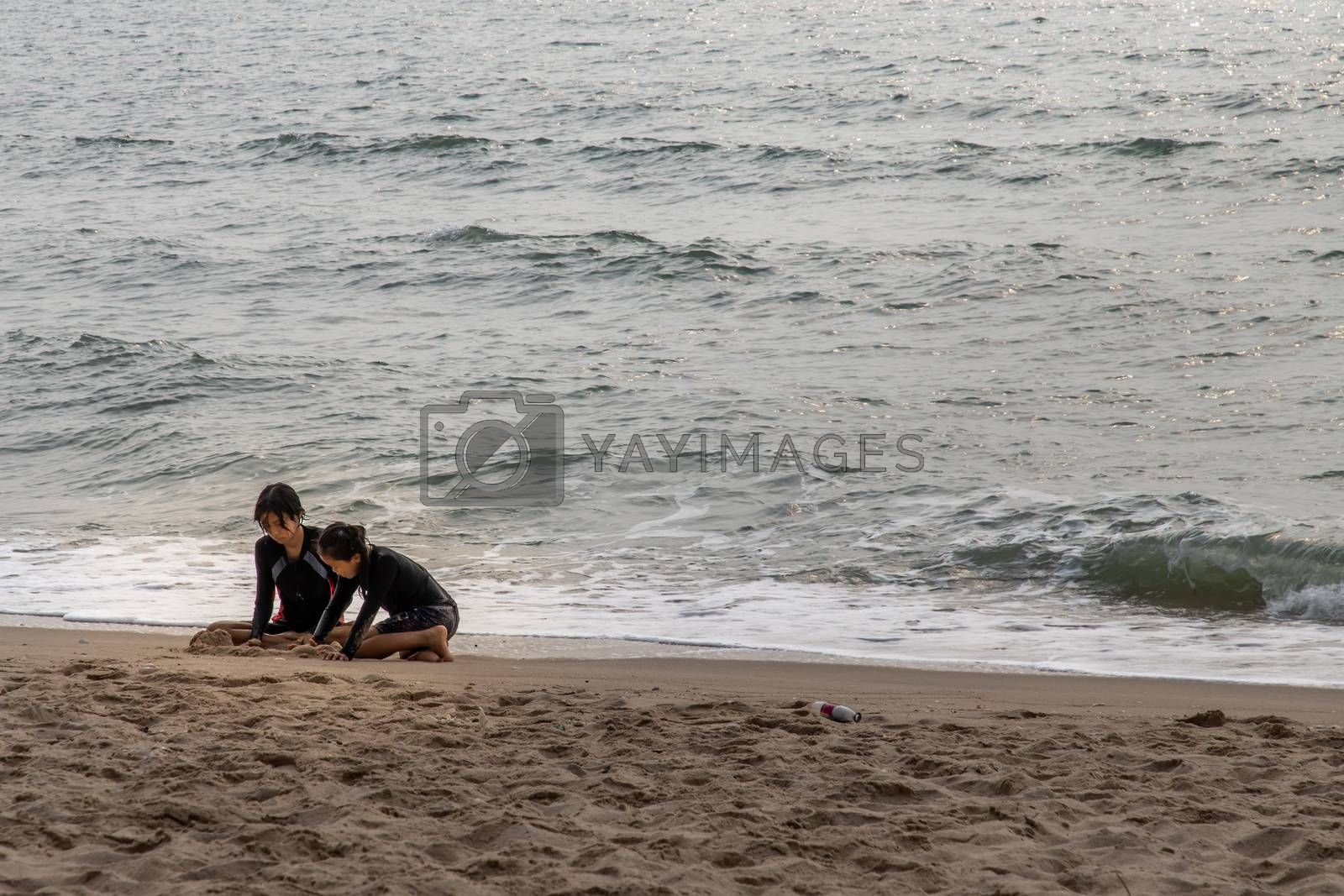 Phetchaburi,Thailand - Mar 15, 2020 : Two girls playing sand on the tropical beach on a sunny day. Vacation trip. Selective focus.