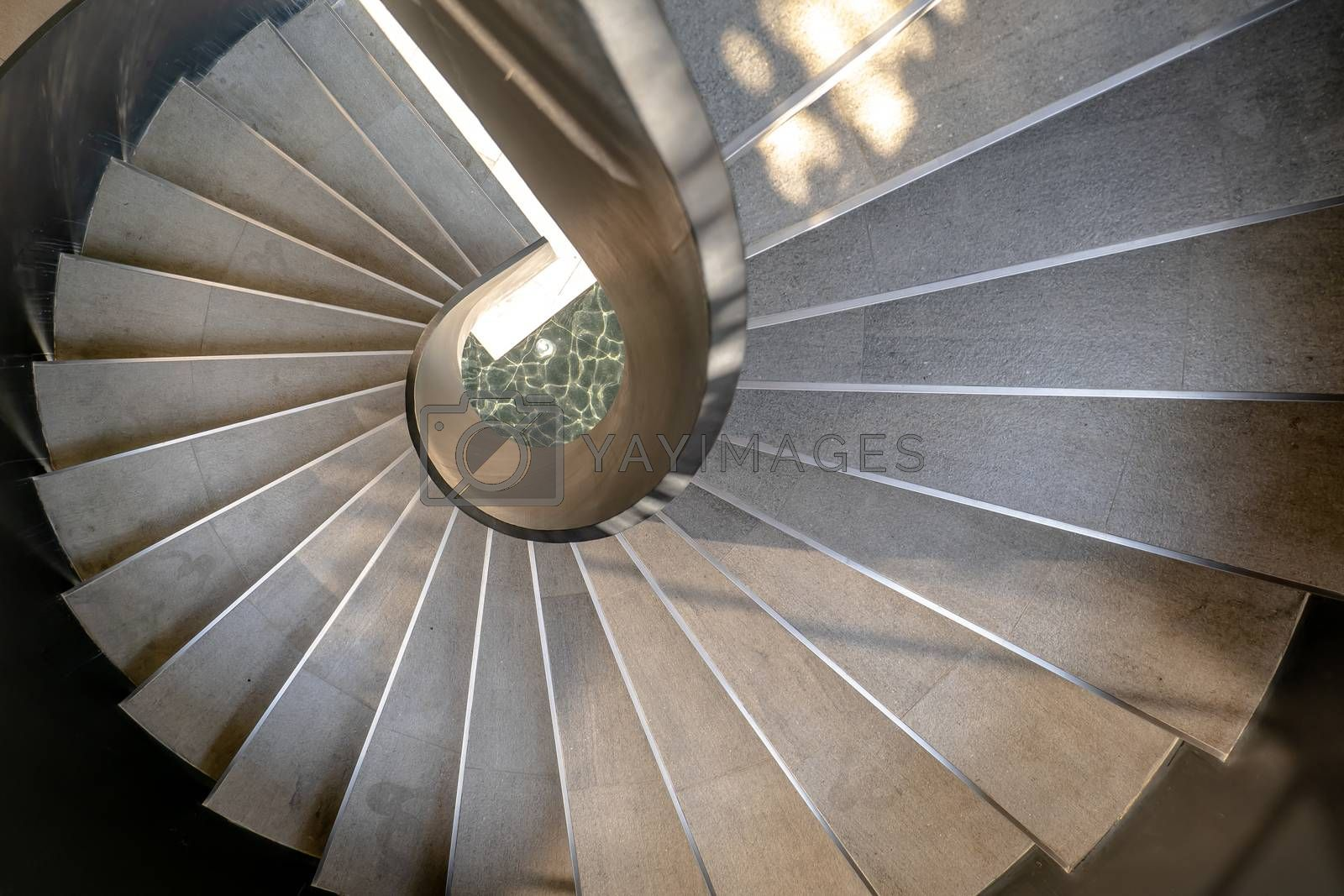 Bangkok, Thailand - May 15, 2020 : Upside view of a spiral staircase pattern. Spiral stairs circle in courtyard architecture. Outdoor ladder decoration interior. Selective focus.