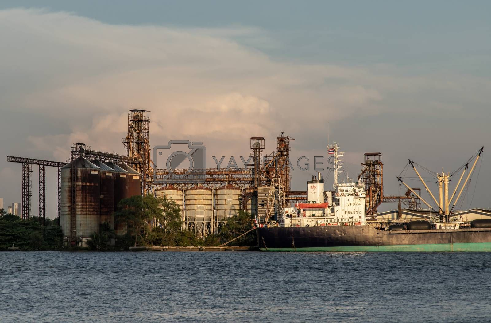 Bangkok, Thailand - 26 Mar 2020 : A petroleum refinery with storage tanks, distillation towers and other chemical synthesis and production equipment with the boat parking near riverside in bangkok.