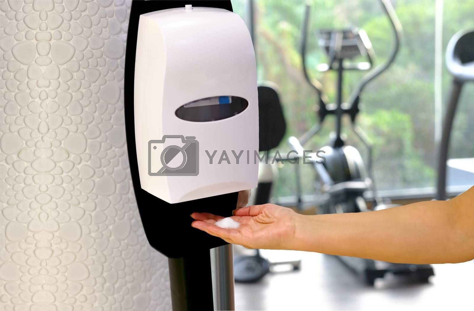 Closeup of Hands under the automatic alcohol dispenser with fitness center background. Fitness gym protection virus concept after Fitness isolation period.