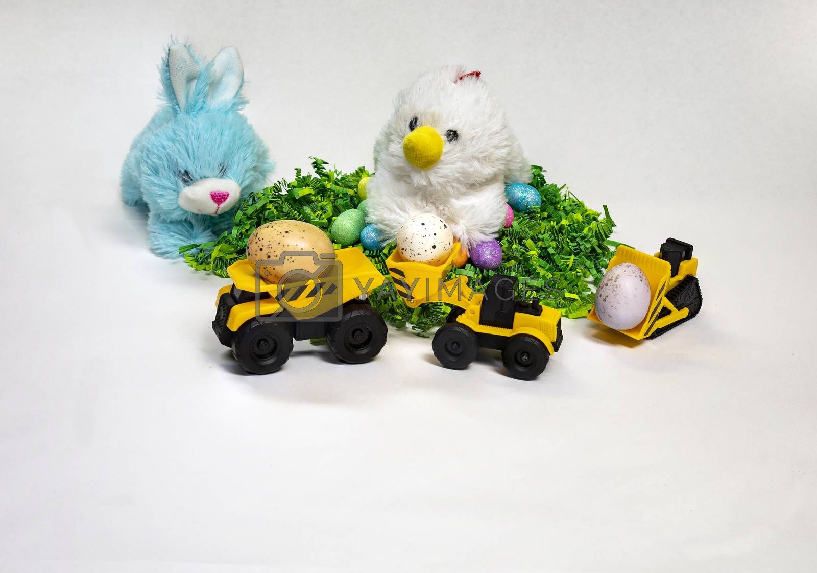 Easter themed photo of stufed bunny and hen with decorated Easter eggs and a child's toy construction vehicles.