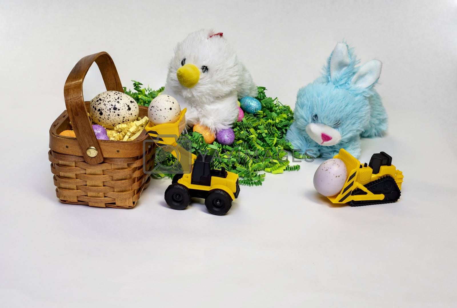 Easter themed photo of stufed bunny and hen with decorated Easter eggs, a basket,  and a child's toy construction vehicles.