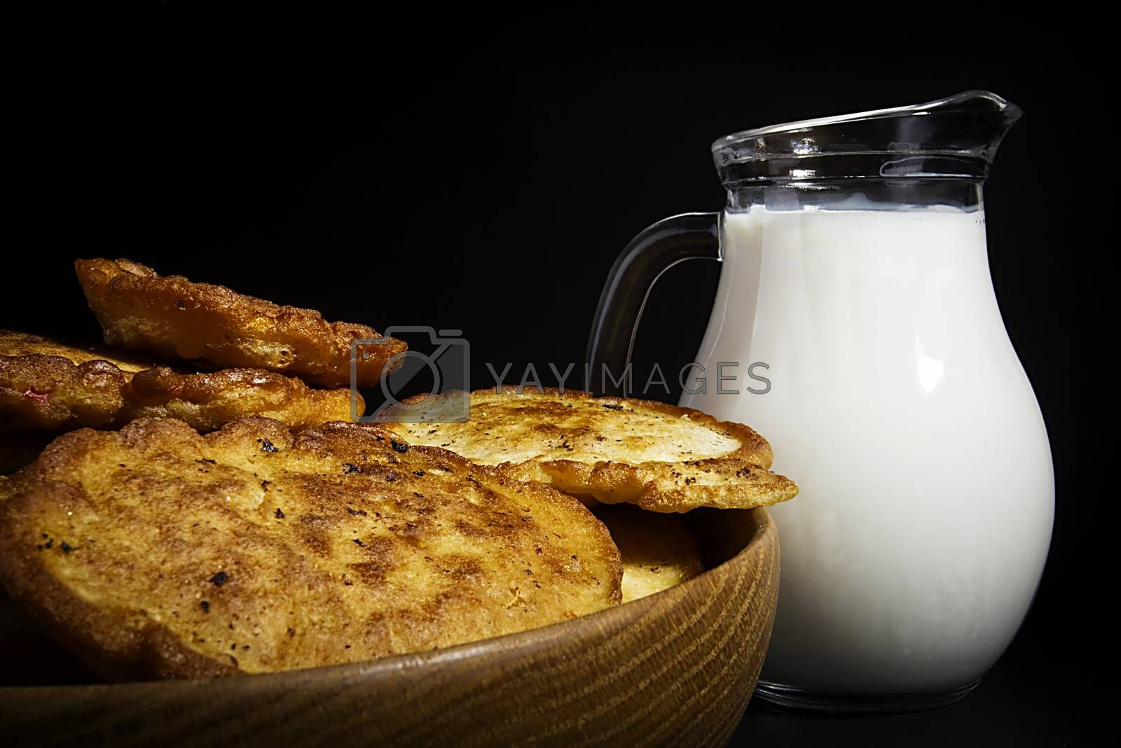 Corn pancakes and milk in a glass jar