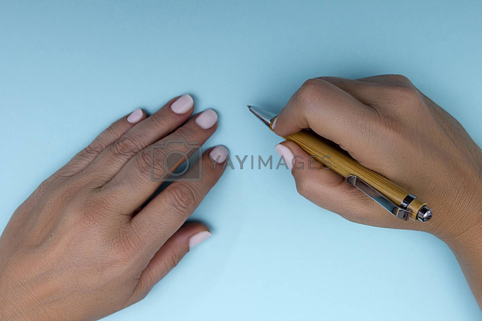 Pen in female hands on a blue background