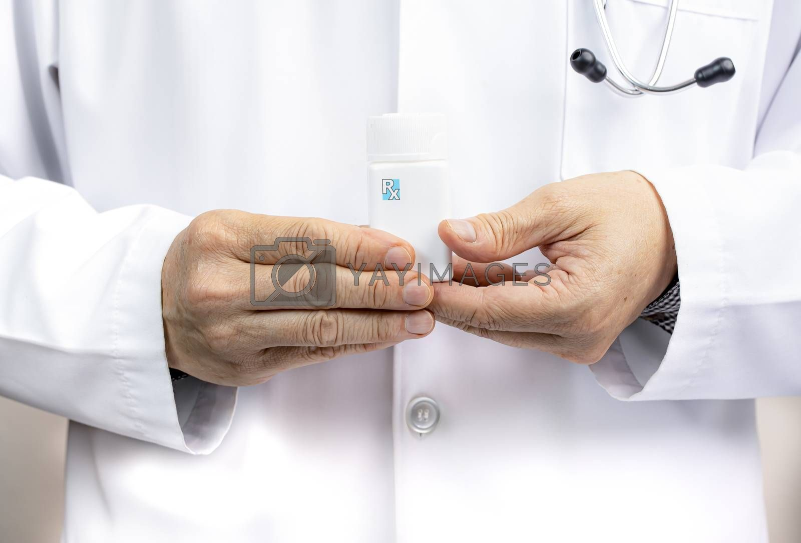 A male doctor holding a white medicine bottle.