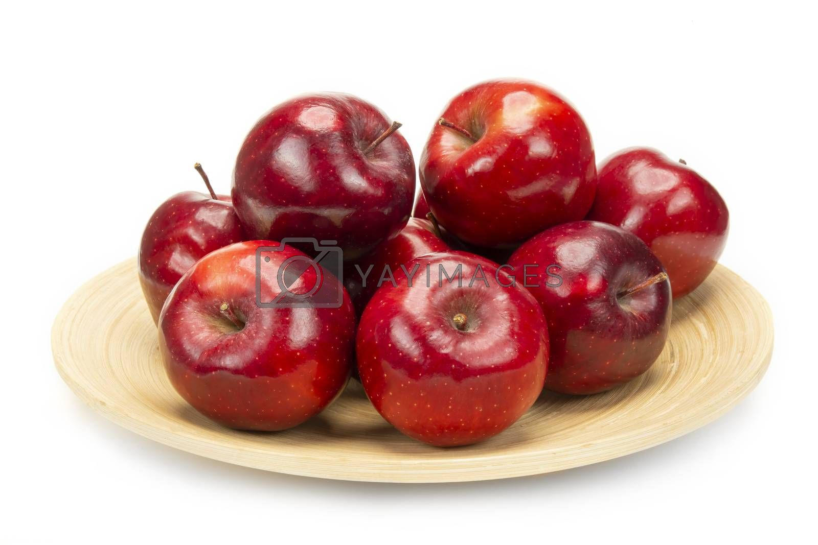 A bunch of fresh red apples on a bamboo plate, isolated on white background.