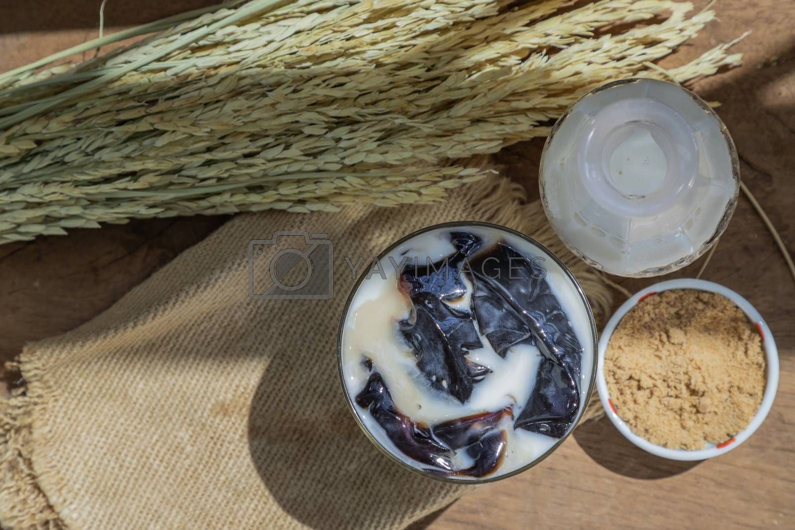 A Glass of Fresh milk grass jelly Dessert herbal gelatin or Jelly black with milk and brown sugar on the wooden background. Sweet delicious dessert chinese style.