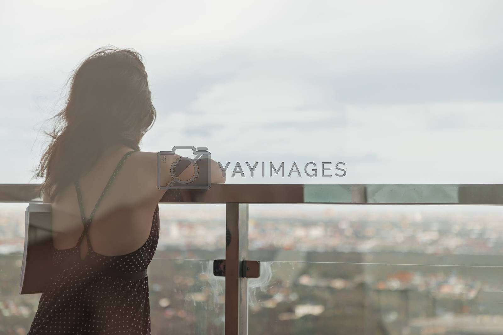 Bangkok, Thailand - Jul 19, 2020 : Young women standing resting and looking through at cityscape with skyscrapers in balcony view with clear sky before sunset. Moments of joy and relaxation atmosphere. Copy space.