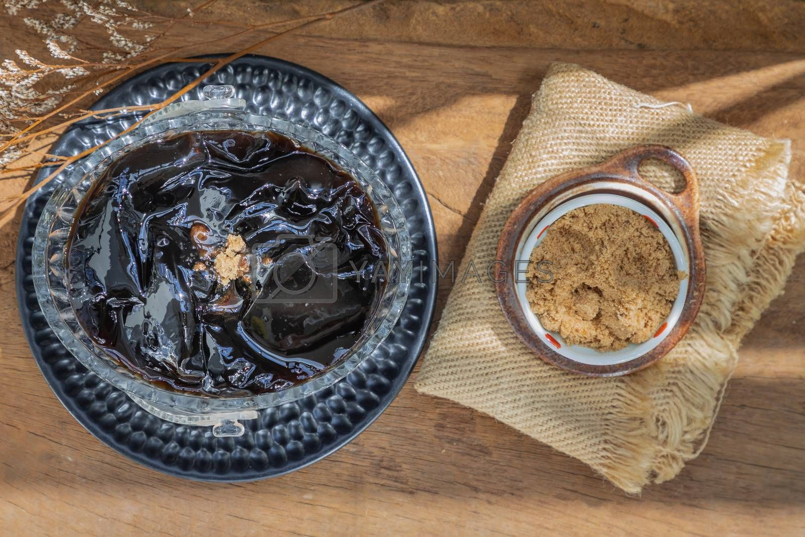 Black grass jelly (Mesona chinensis) Dessert herbal gelatin or jelly black with ice and brown sugar on the wooden background. Sweet delicious dessert chinese style.