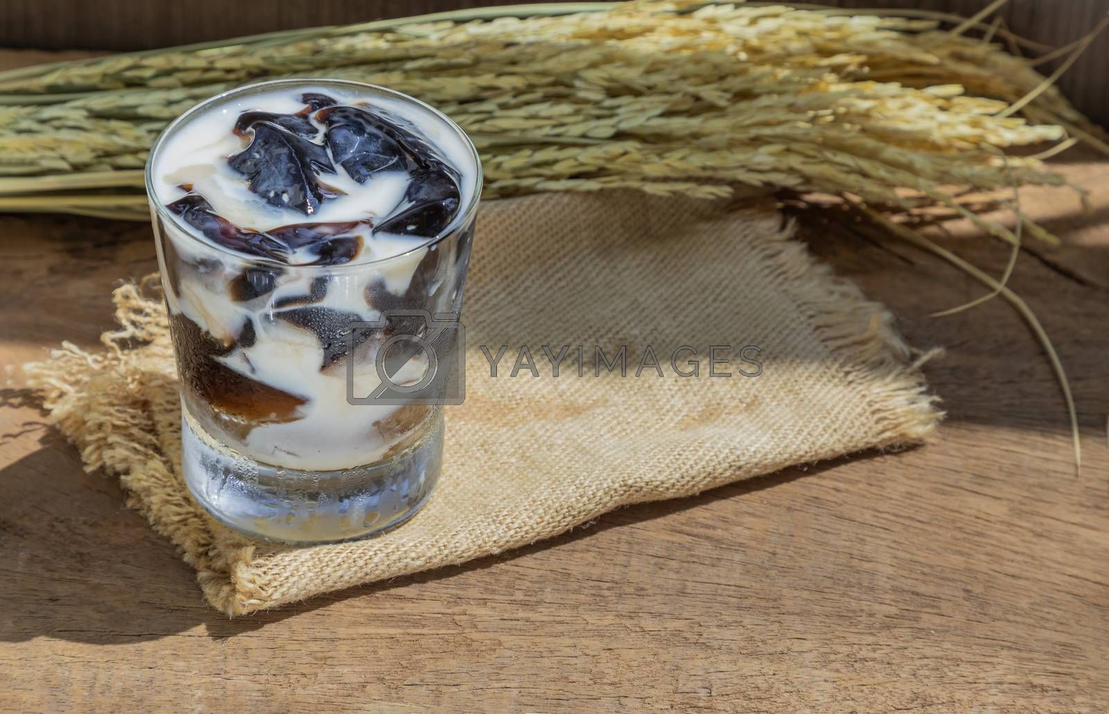 A Glass of Fresh milk grass jelly Dessert herbal gelatin or Jelly black with milk on the wooden background. Sweet delicious dessert chinese style.