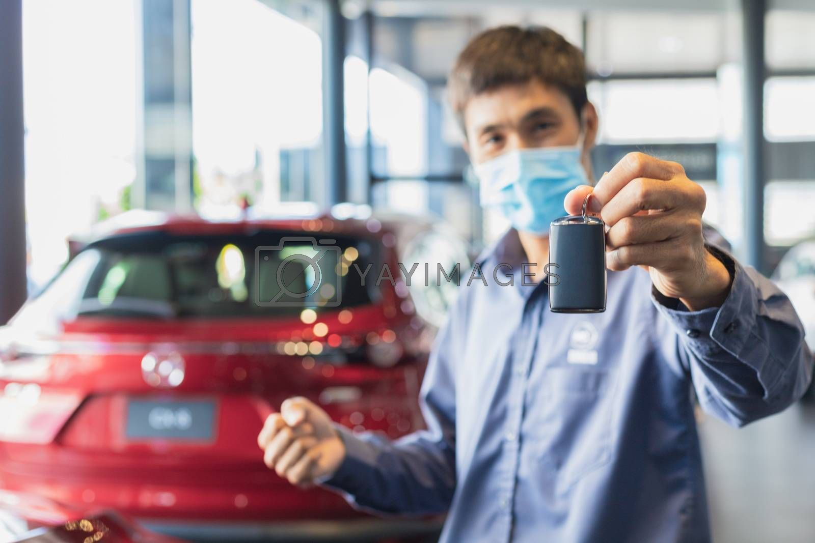 Asian man blurred holding in key car in dealership service maintenance insurance and receives the keys from the customer for send happiness car to travel