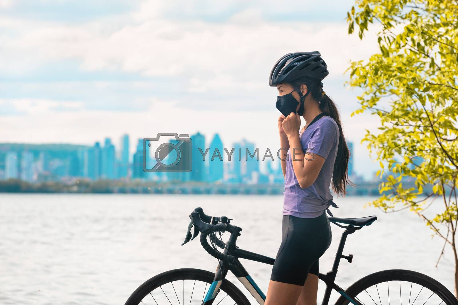 Wearing covid-19 mask while riding bike. Sport cyclist woman biking putting on face mask for Covid-19 prevention during summer outdoor leisure exercise activity. Fitness outside by Maridav