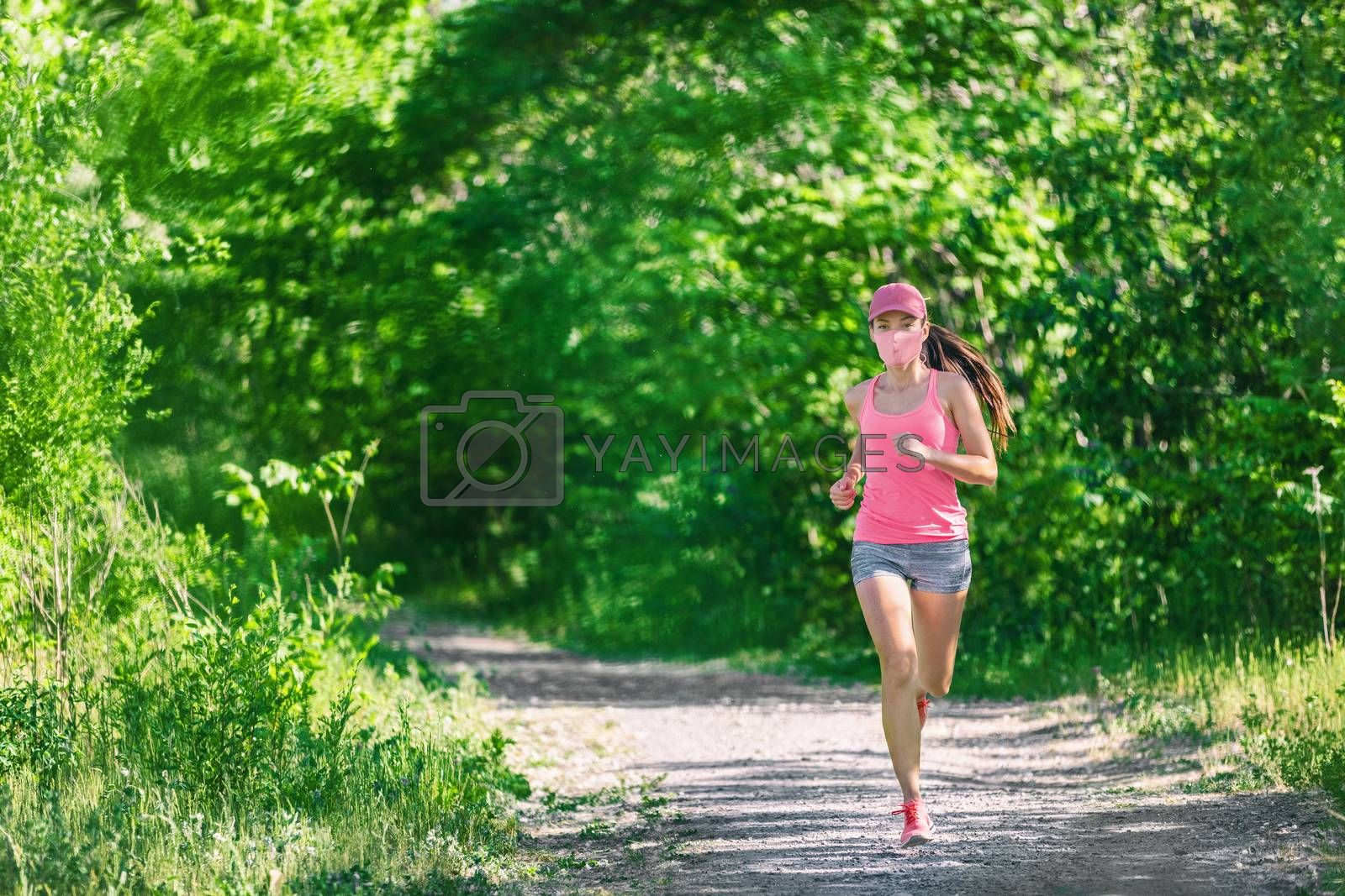 Mask corona virus COVID-19 running runner athlete wearing mask jogging outside on run workout in summer park nature. Sport lifestyle asian young woman.