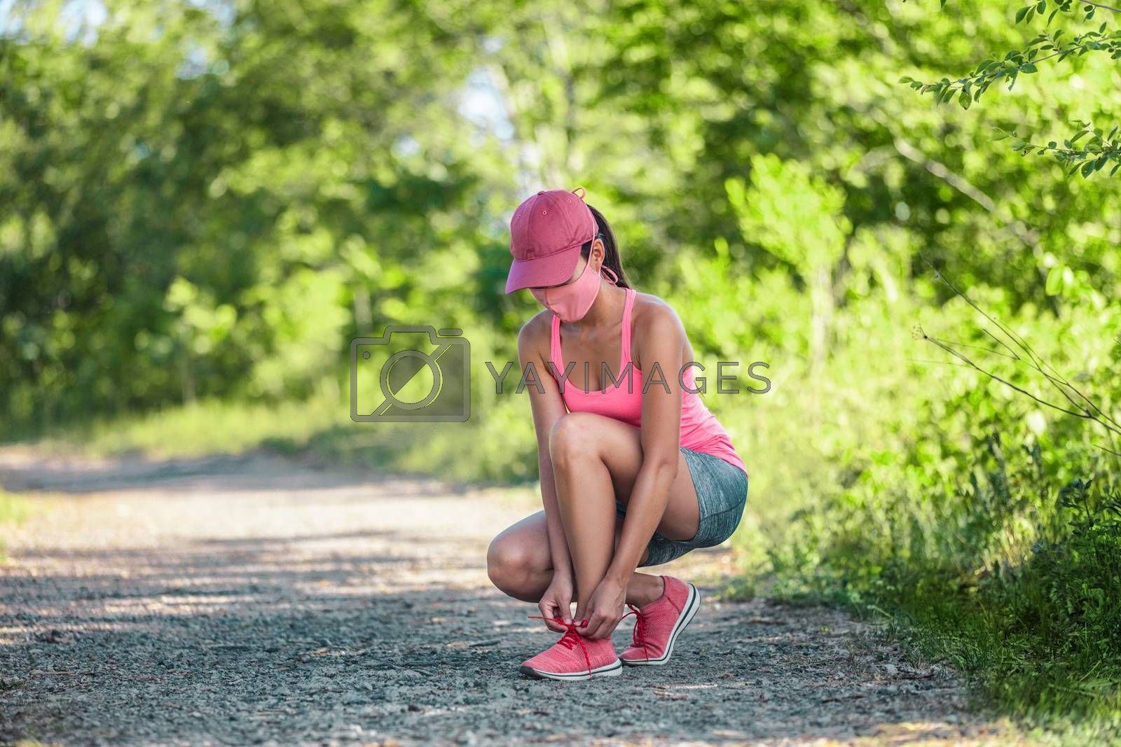 Fitness woman wearing COVID-19 face mask getting ready to do run exercise lacing running shoes for outdoor jogging during coronavirus.
