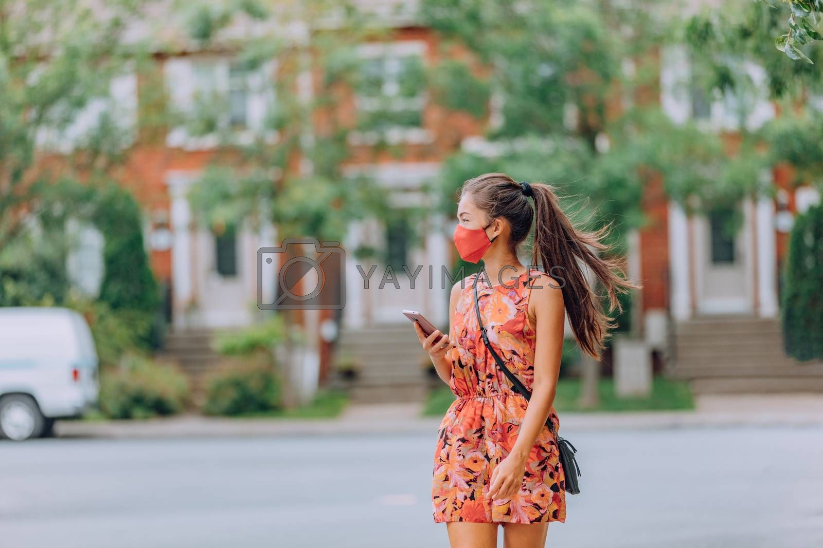 COVID-19 girl walking in city street wearing face mask. Mandatory wear Asian woman commuting using mobile phone. protection as prevention for coronavirus outside in city park summer lifestyle outdoor. Corona virus.