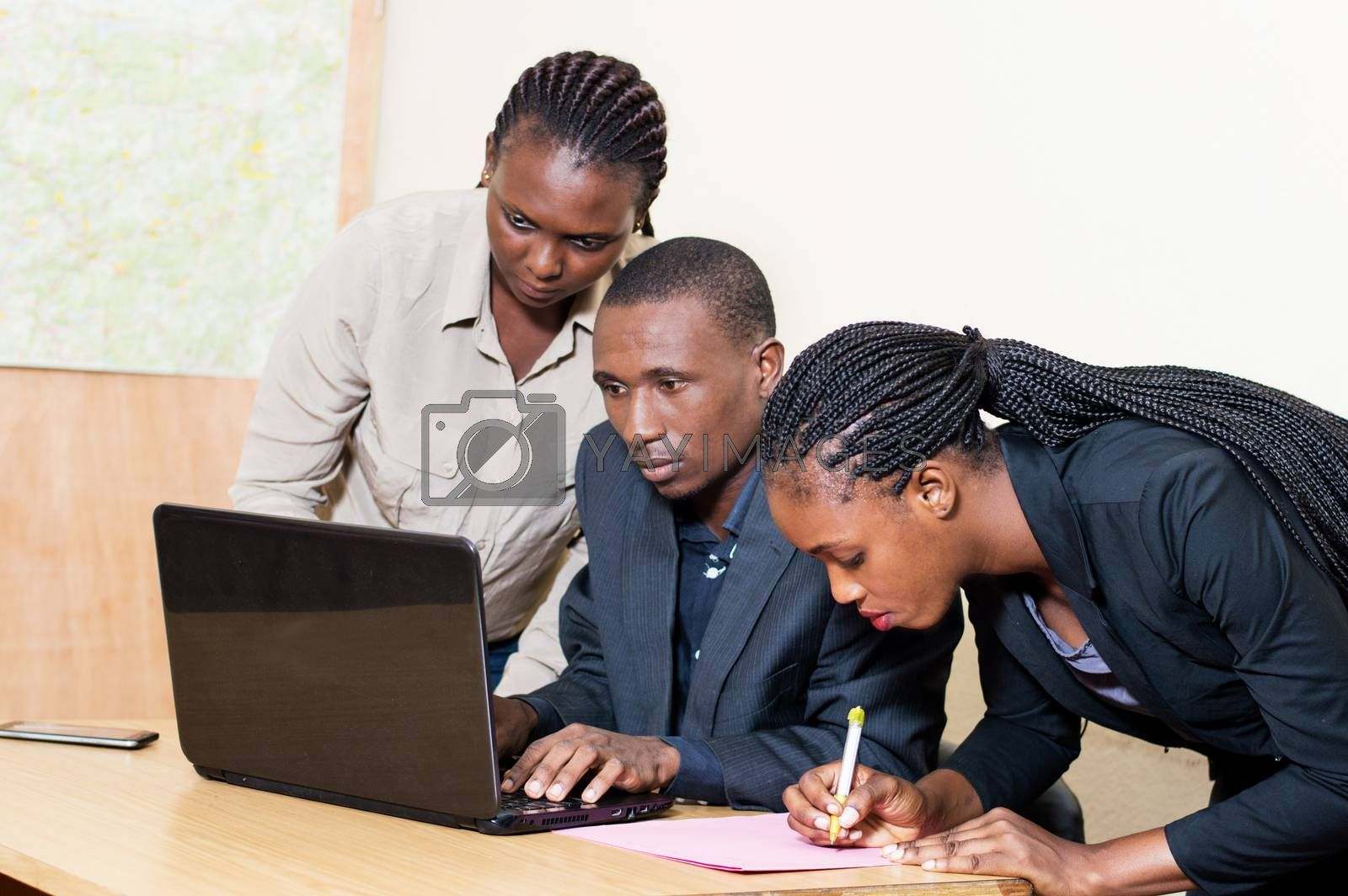 Three business partners working on a laptop in the office.