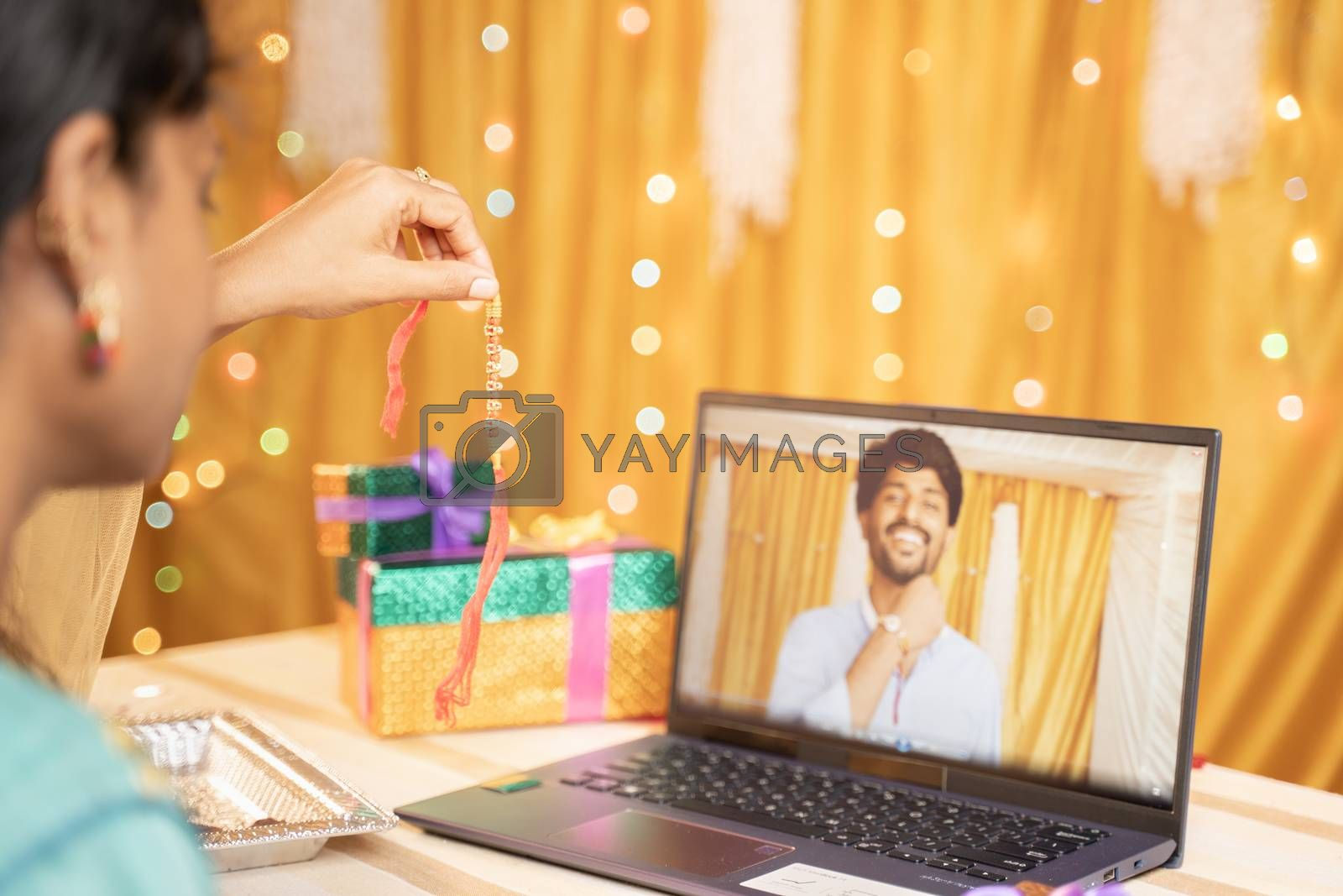 shoulder view of sister video calling her brother to tie rakhi or Raksha Bandhan during festival and showing gift received - Concept of far Rakshabandhan celebration by using technology and internet