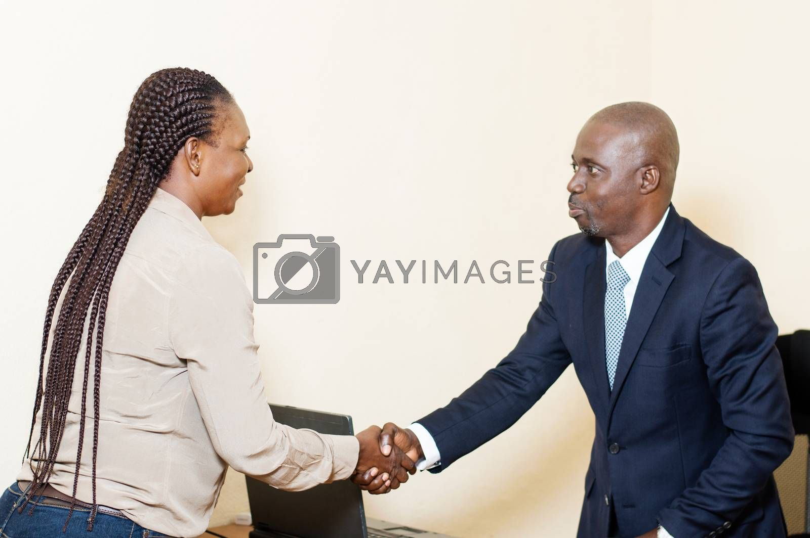 Young businesswoman arrives for a business meeting and greets her colleague before sitting at the office.