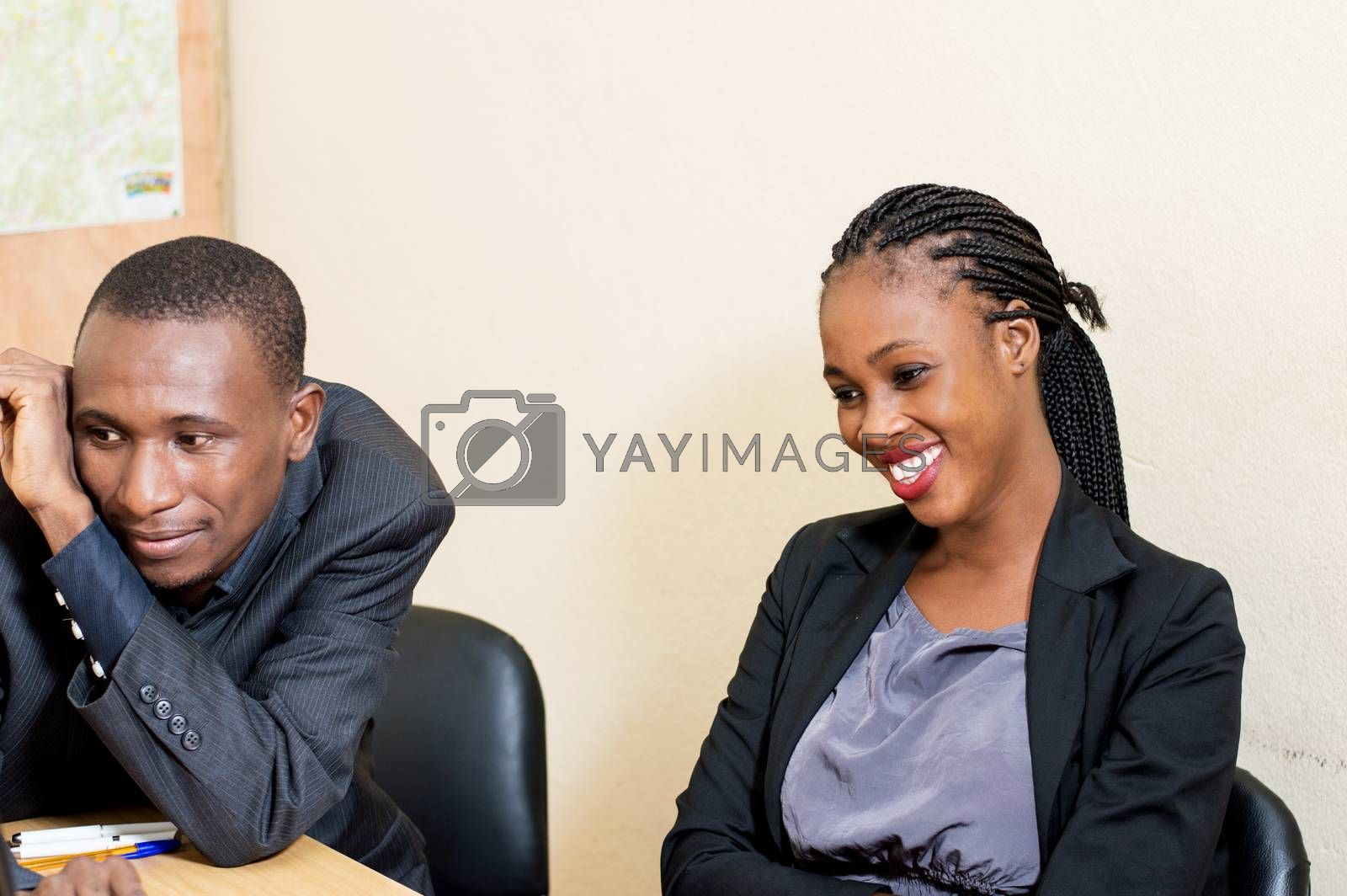 Happy young business people share a laptop at the office.