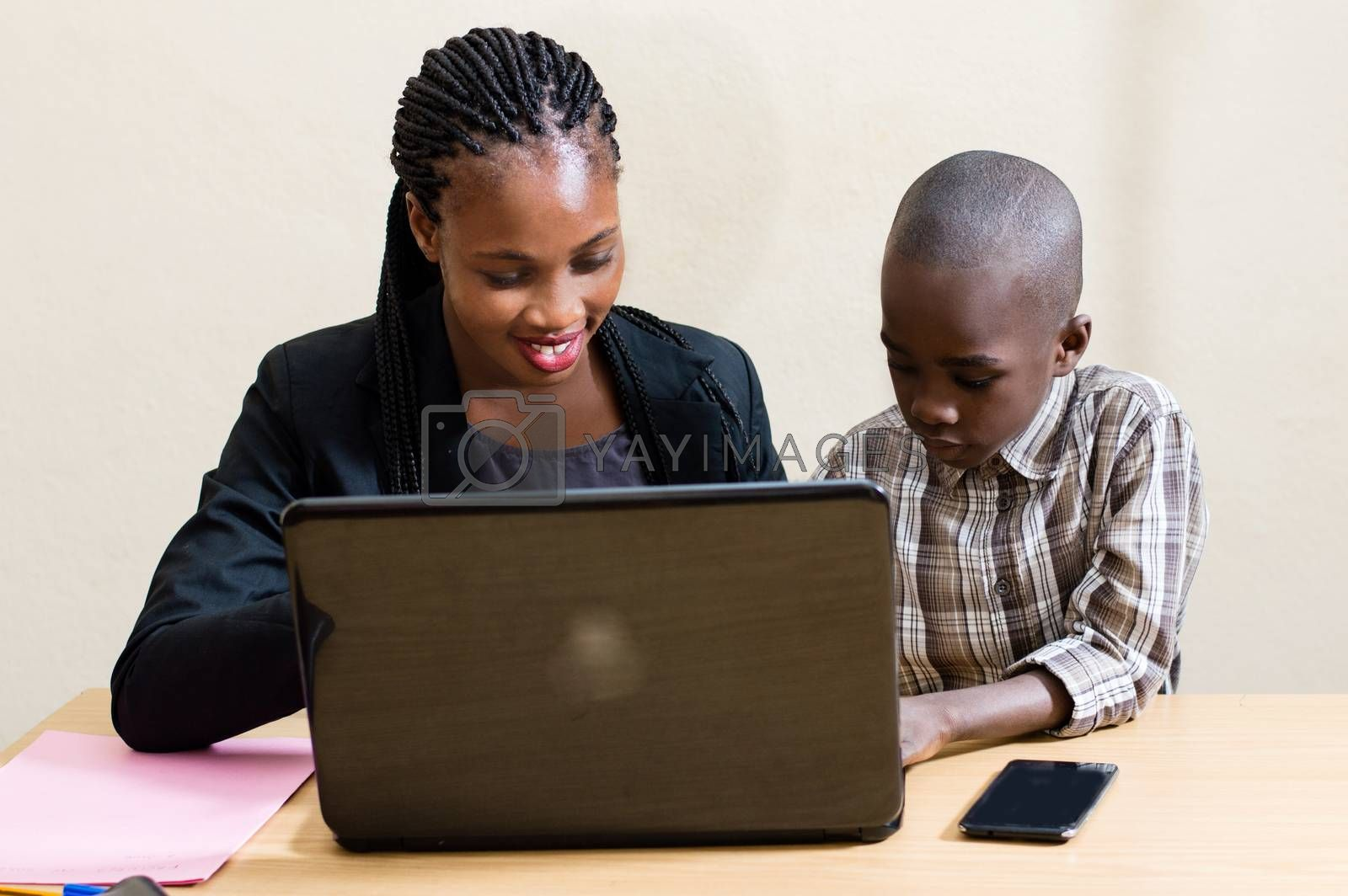 Smiling young woman learns computer skills from child